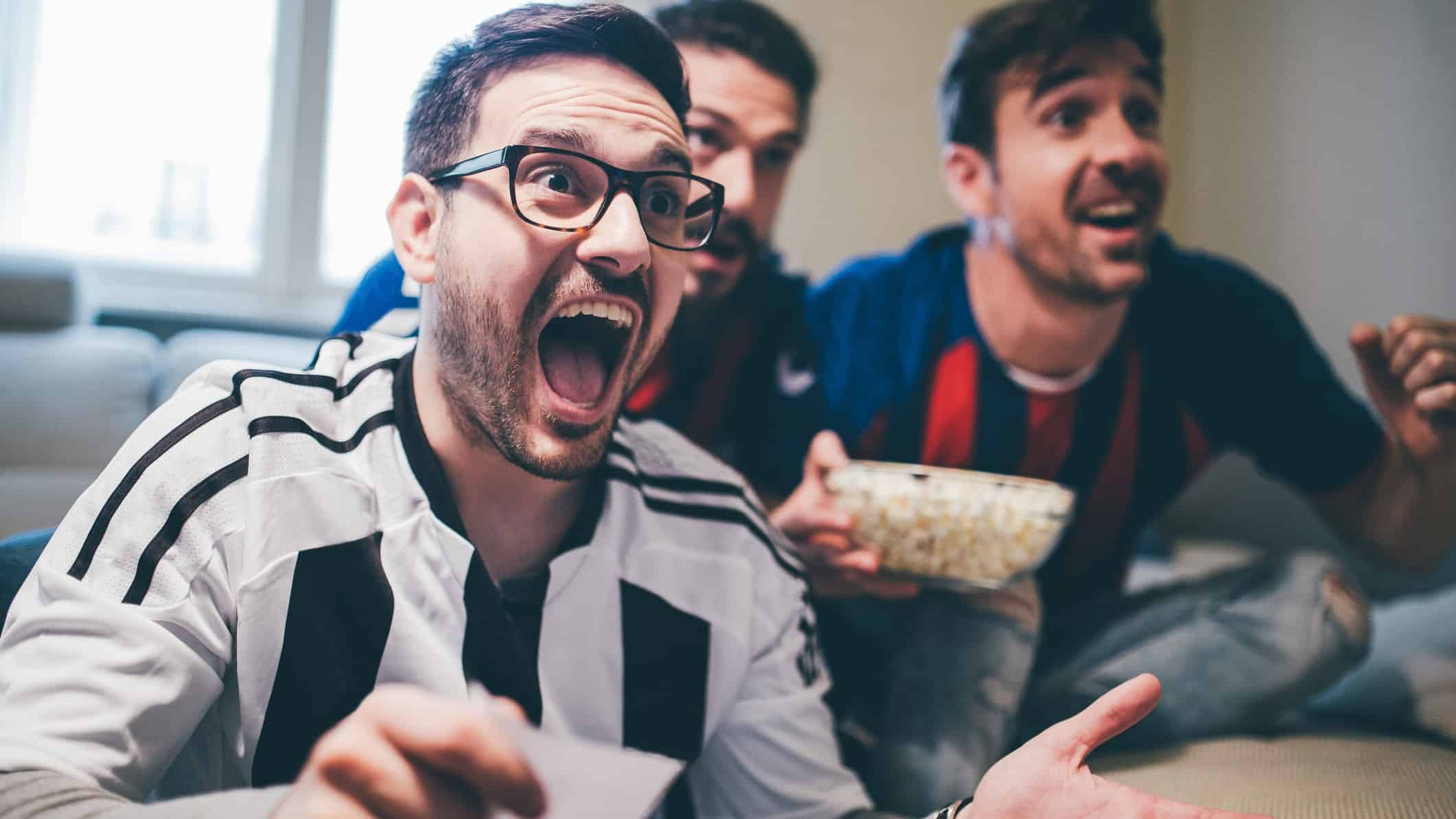 Man holding up betting slip and cheering along with two friends in front of TV