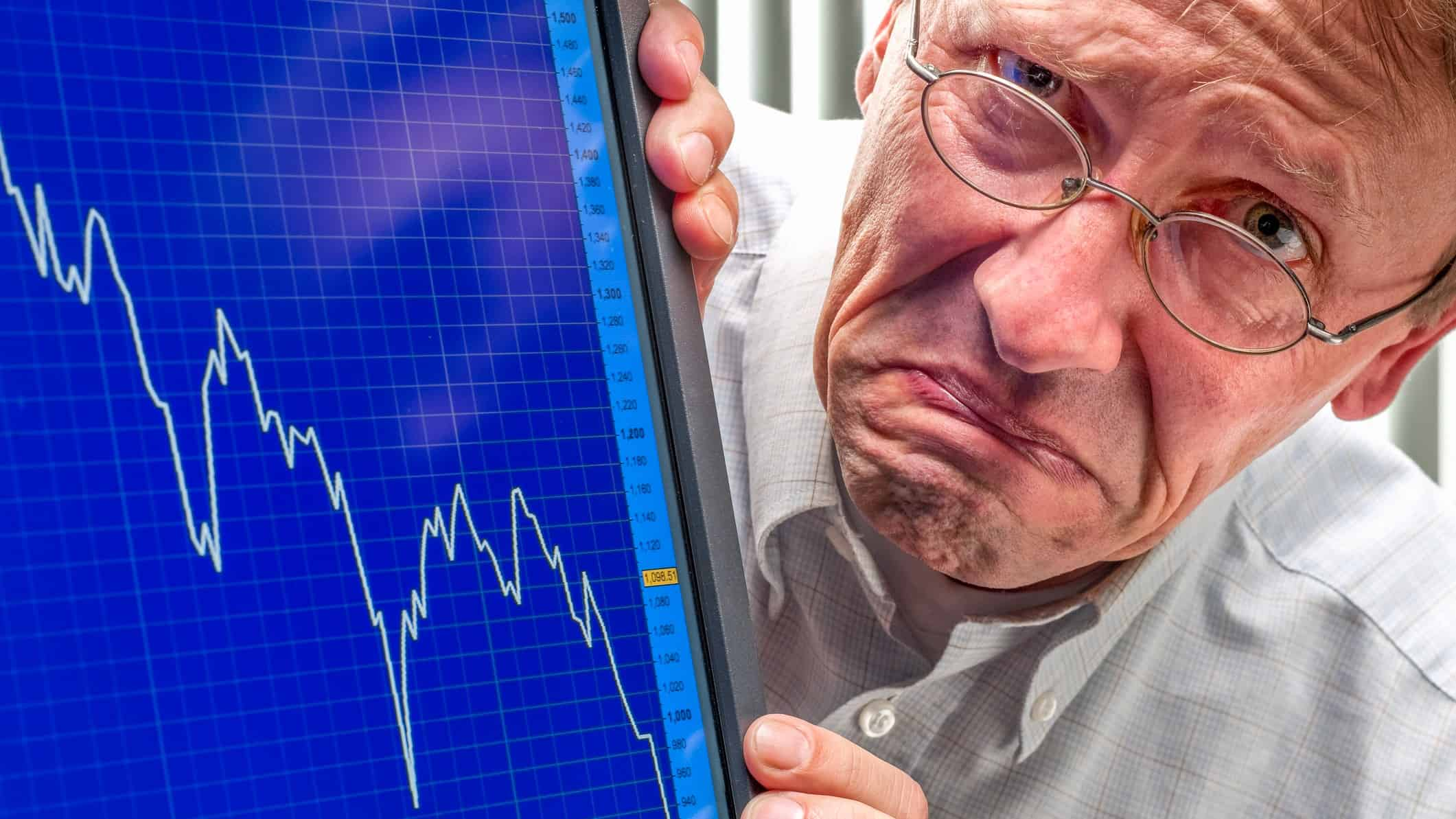 man grimaces next to falling stock graph