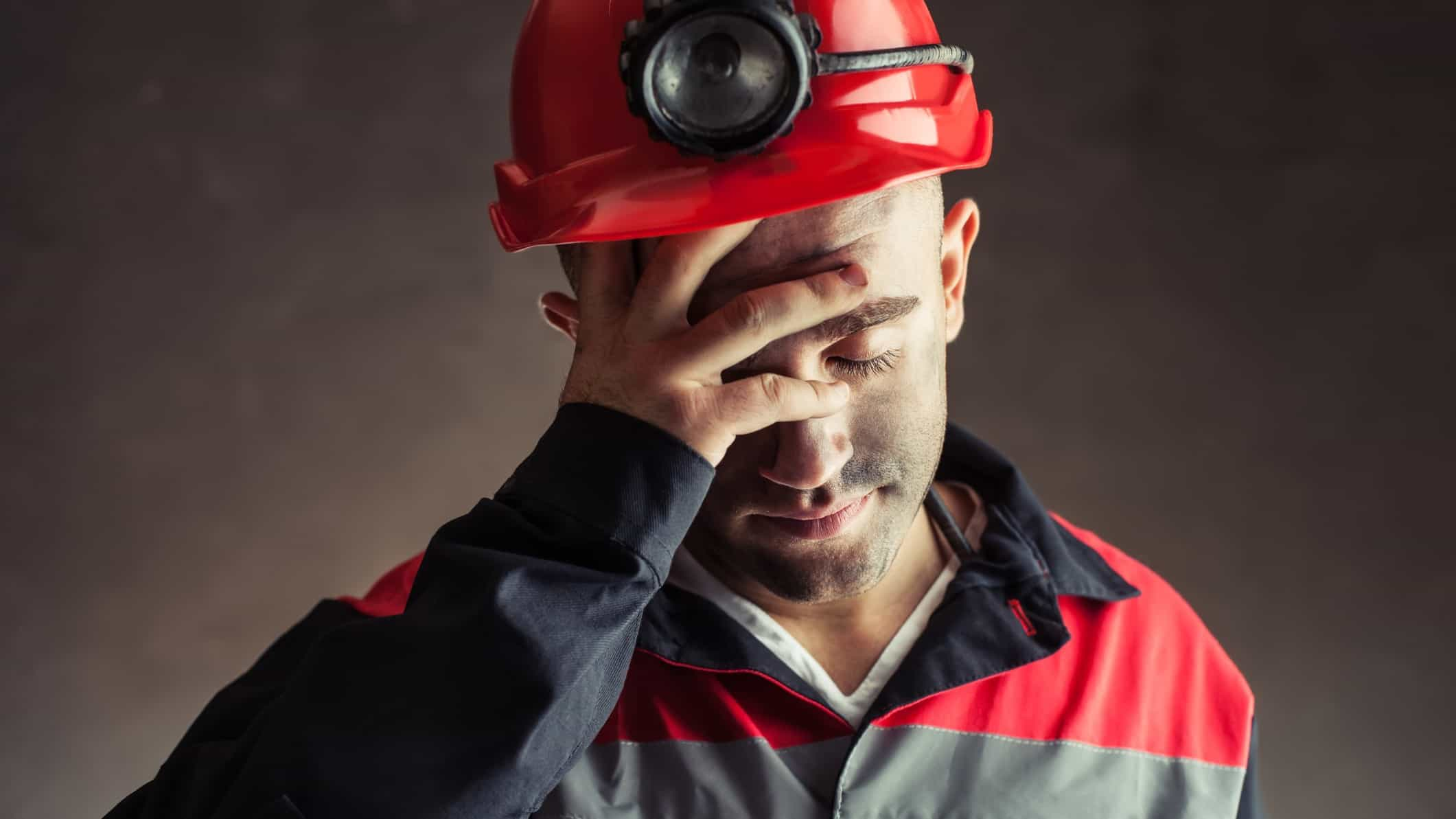 A sad miner holds his head in his hands