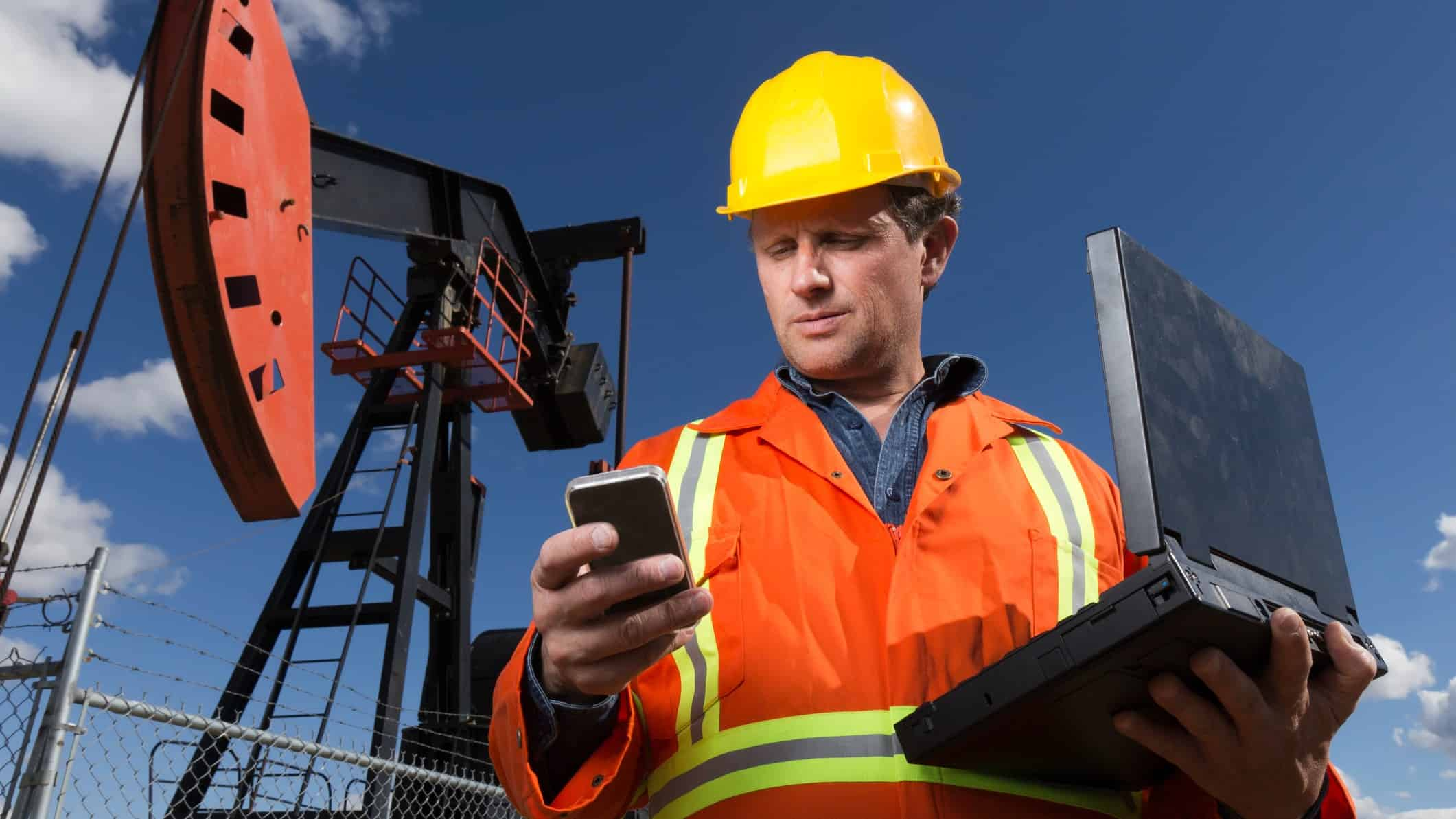 Oil miner with laptop and phone at mine site