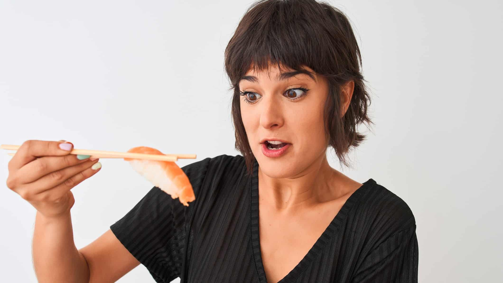 A surprised woman holds a piece of salmon with chopsticks