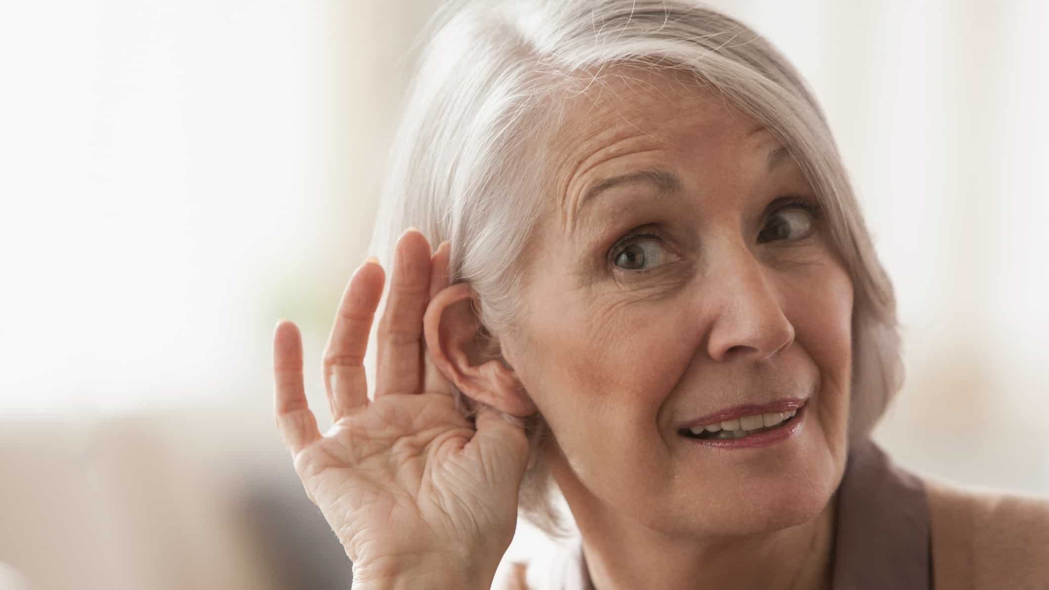 older woman tries to listen by cupping ear