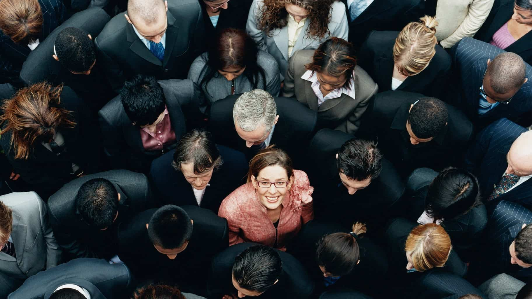 A woman in a crowd of executives stands out as she looks up and smiles