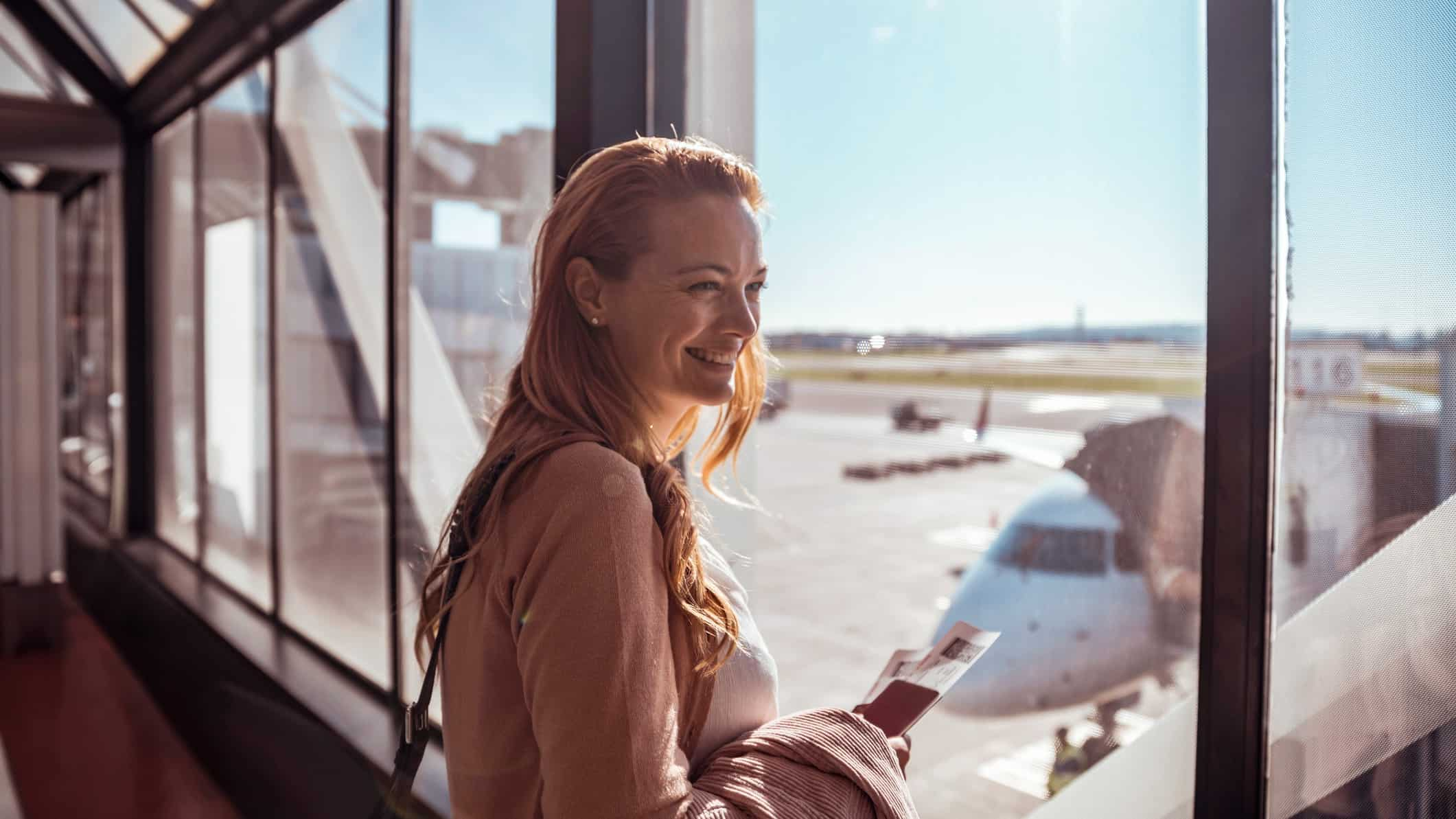 A female traveller stands in the terminal, ready to board her plane.
