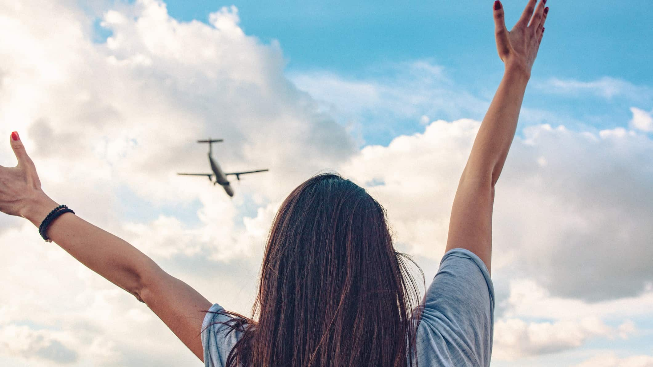 A woman looks up at a Qantas plane flying in the sky with arms outstretched.