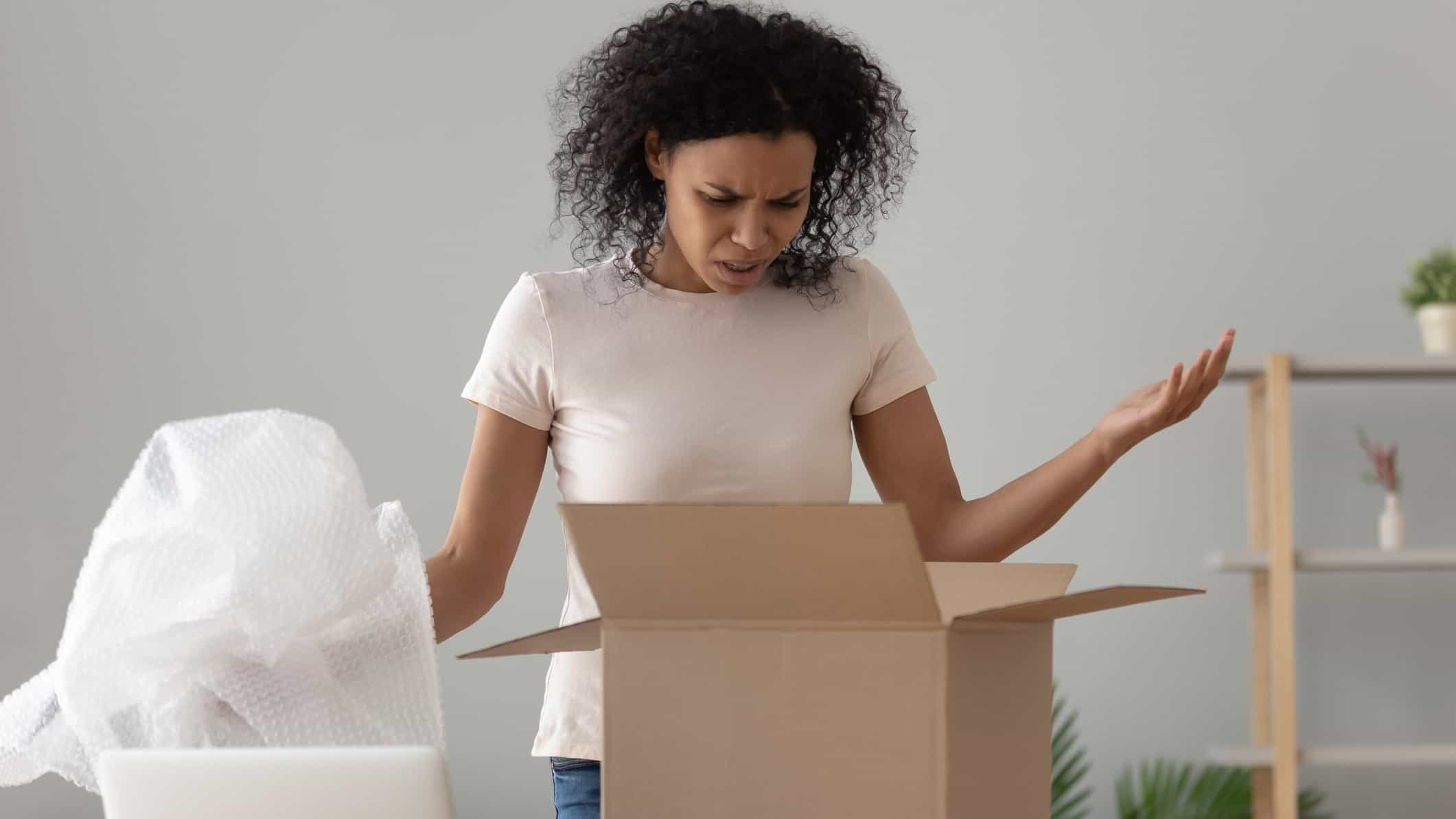 a woman looks disappointed with a package she has unpacked holding her arms up at a box with bubble wrap beside it.