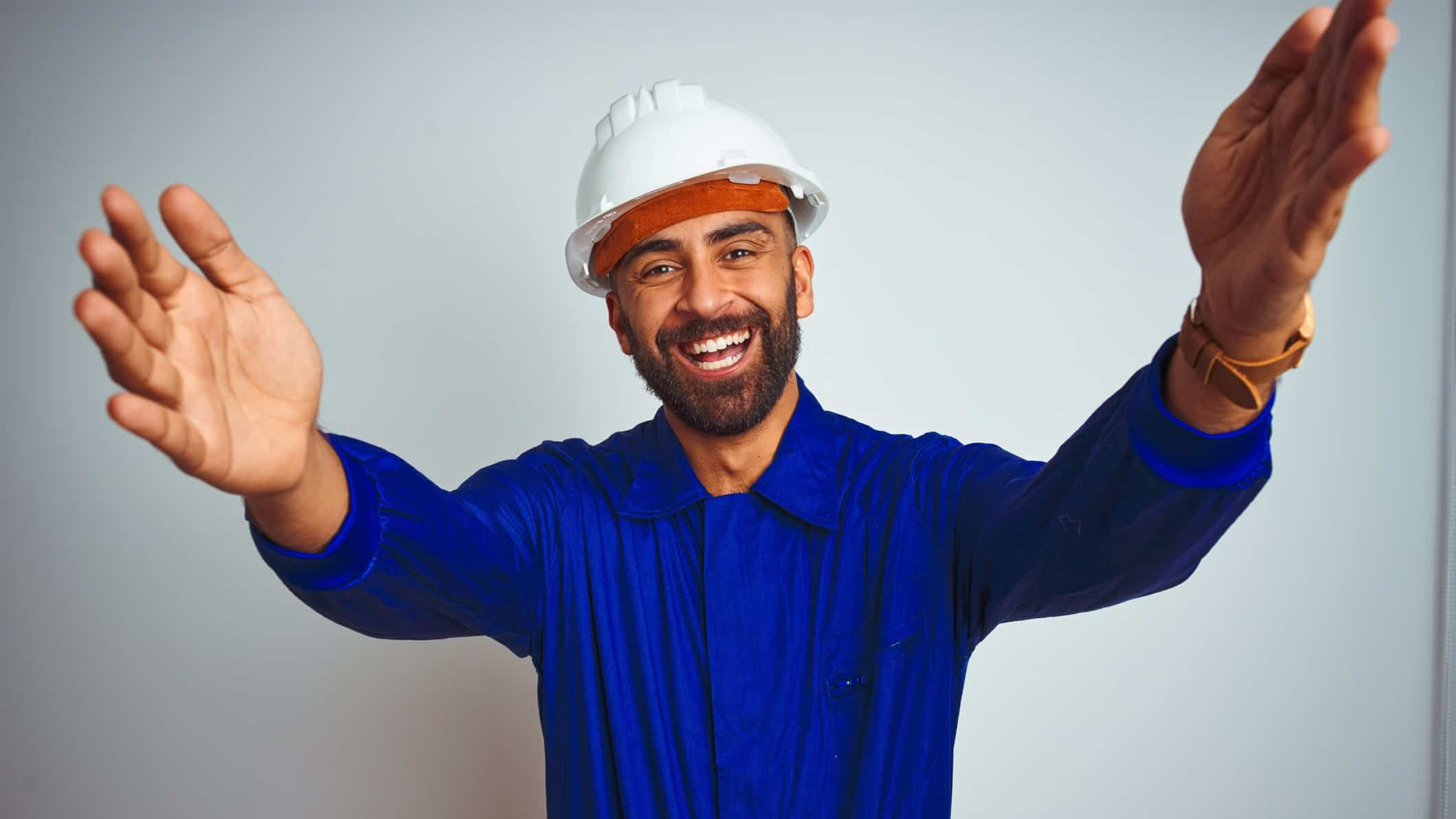 a man in a hard hat and overalls raises his arms and holds them out wide as he smiles widely in an optimistic and welcoming gesture.