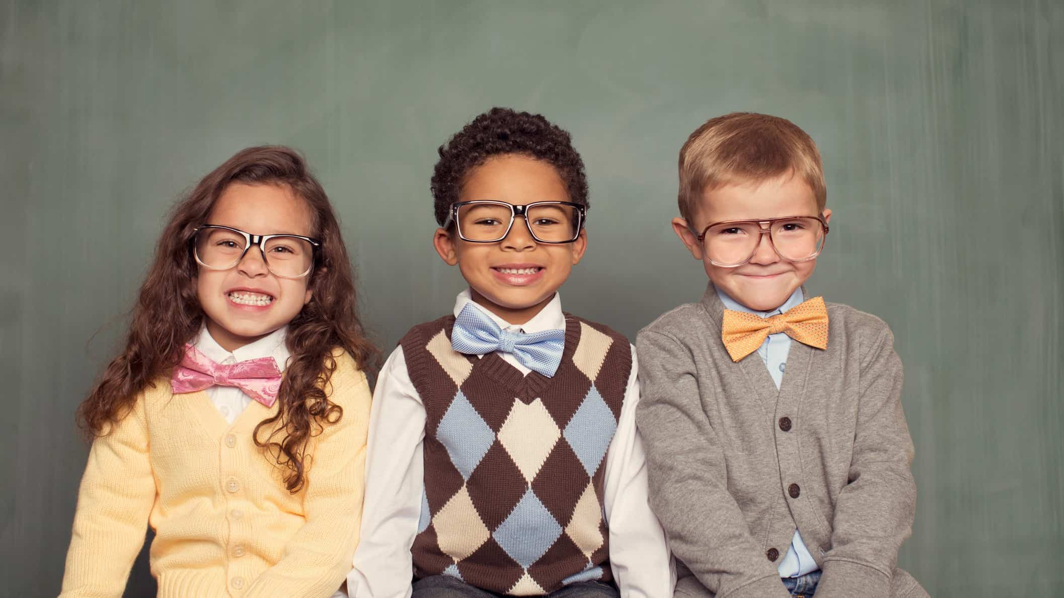 a group of smart looking kids, wearing formal clothes and all with spectacles, sit in a line and smile charmingly.