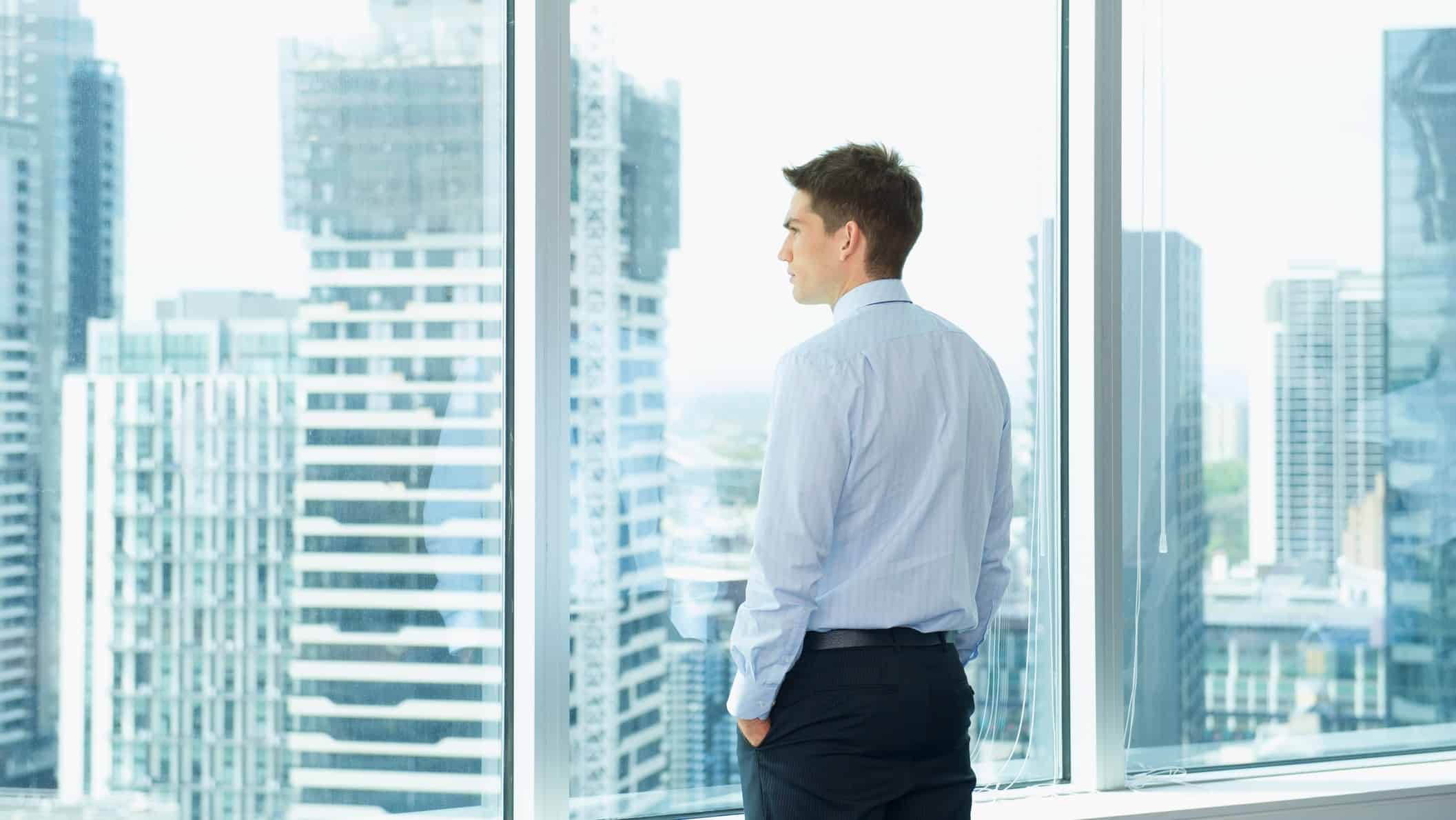 a man with hands in pockets and a serious look on his face stares out of an office window onto a landscape of highrise office buildings in an urban landscape