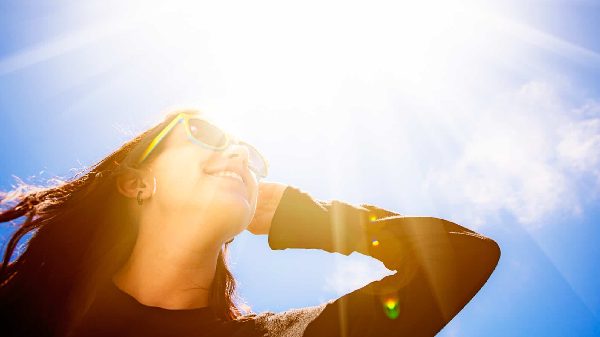 a woman wears sunglasses as she gazes up towards a bright sun with its rays extending to the far corners of the sky above her.