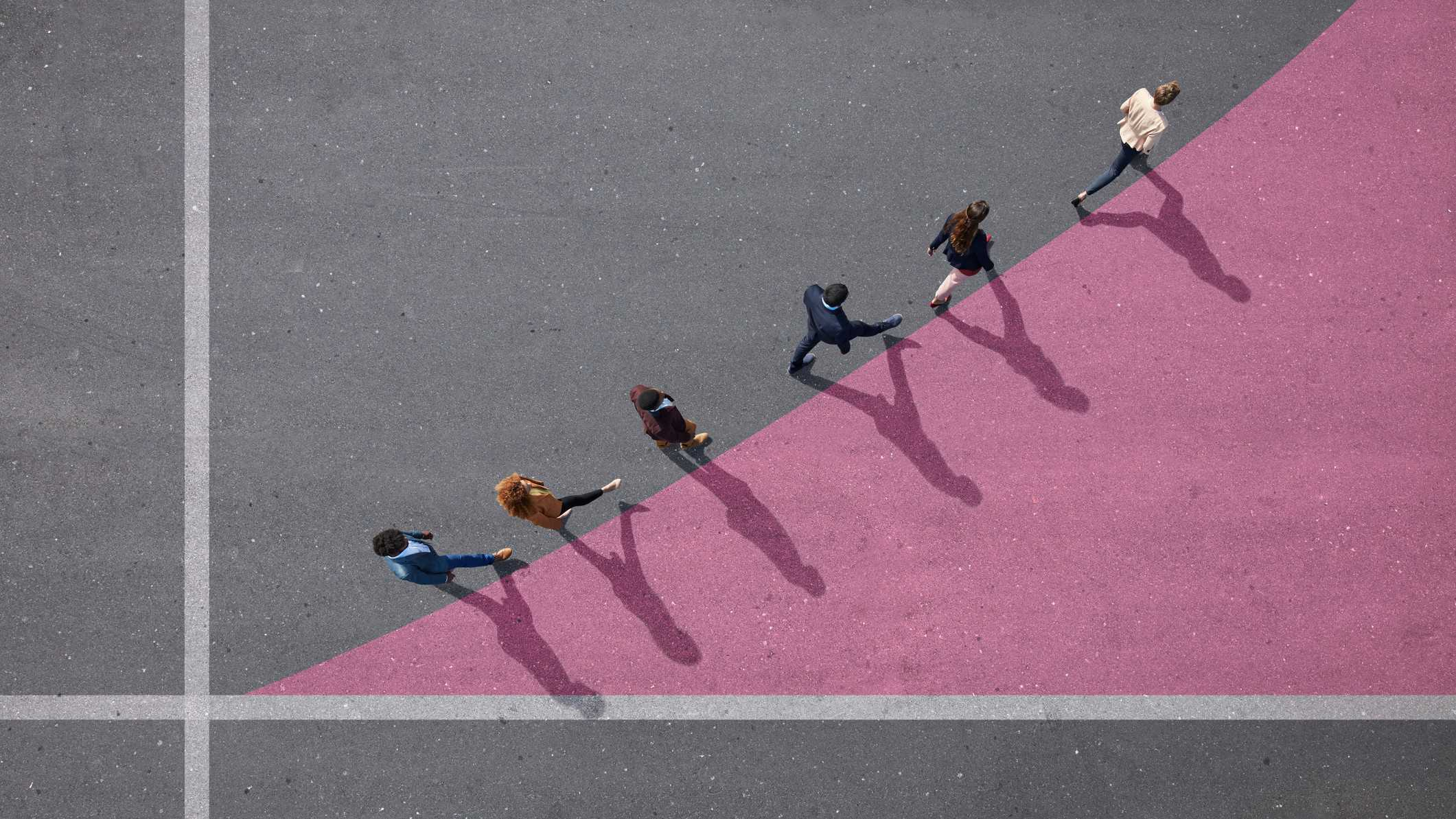 a view from above of six people walking along a curved upward line drawn on the ground between two axes.