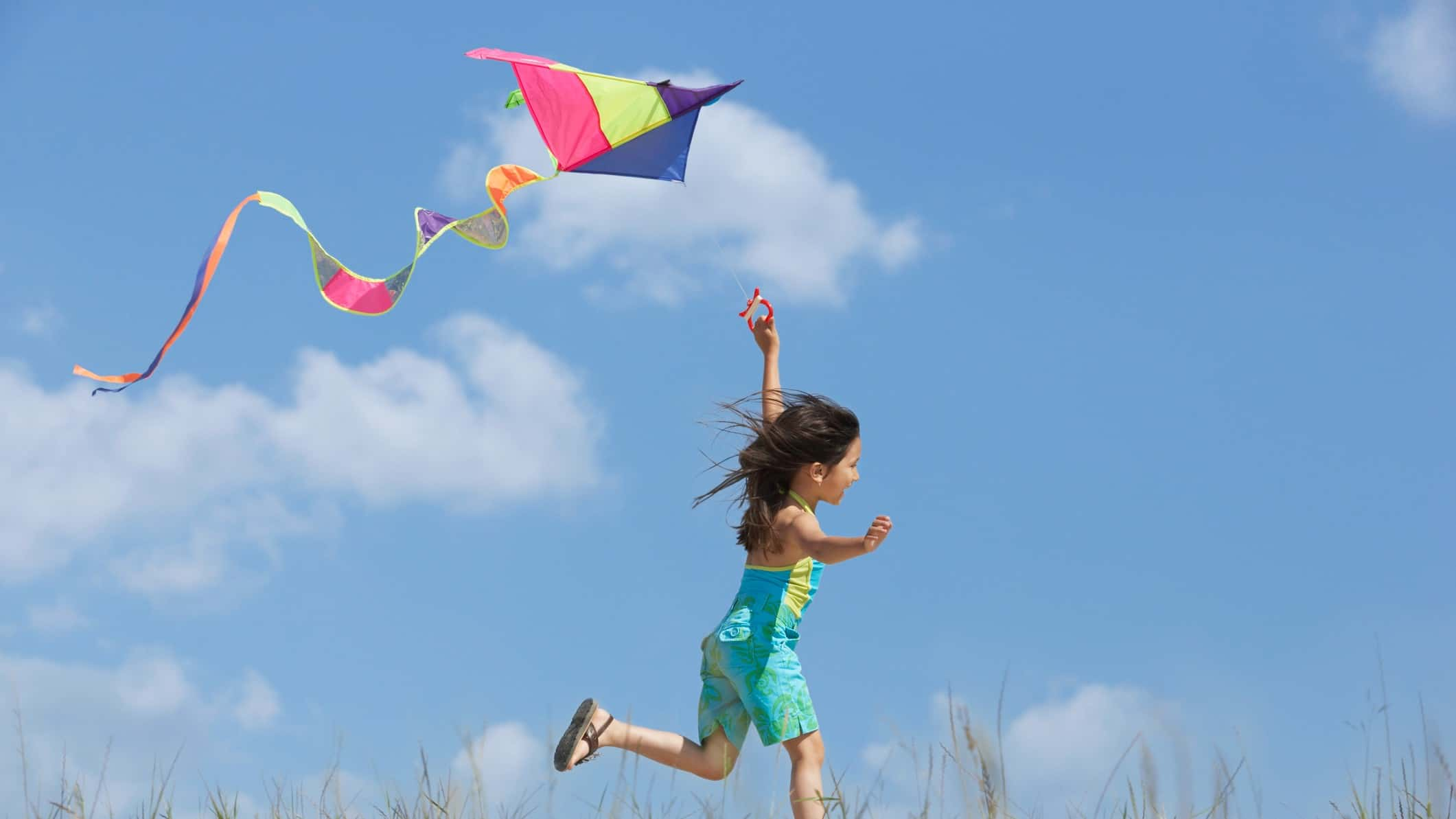 A girl runs along with her kite flying high in the sky.