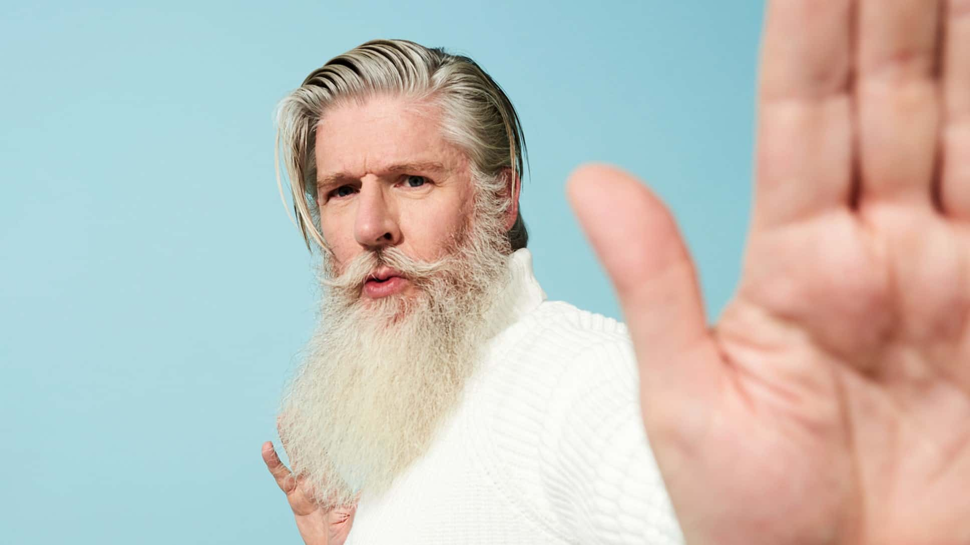 A cool white-bearded man holds his hand up signalling you should halt.