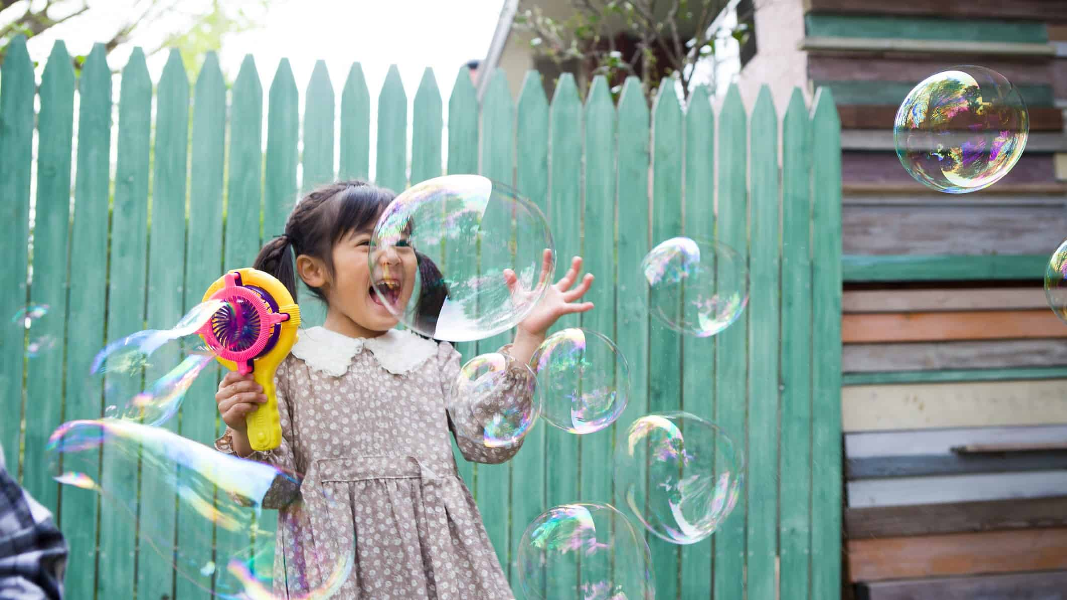 A little Asian girl is so excited by the bubbles coming out of her bubble machine.