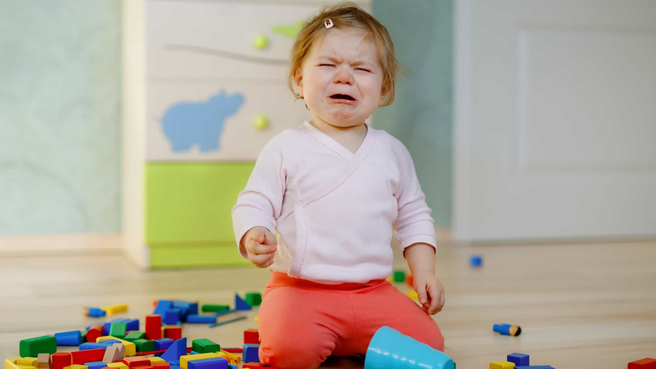 A little kid cries in frustration because her blocks fell over and broke.