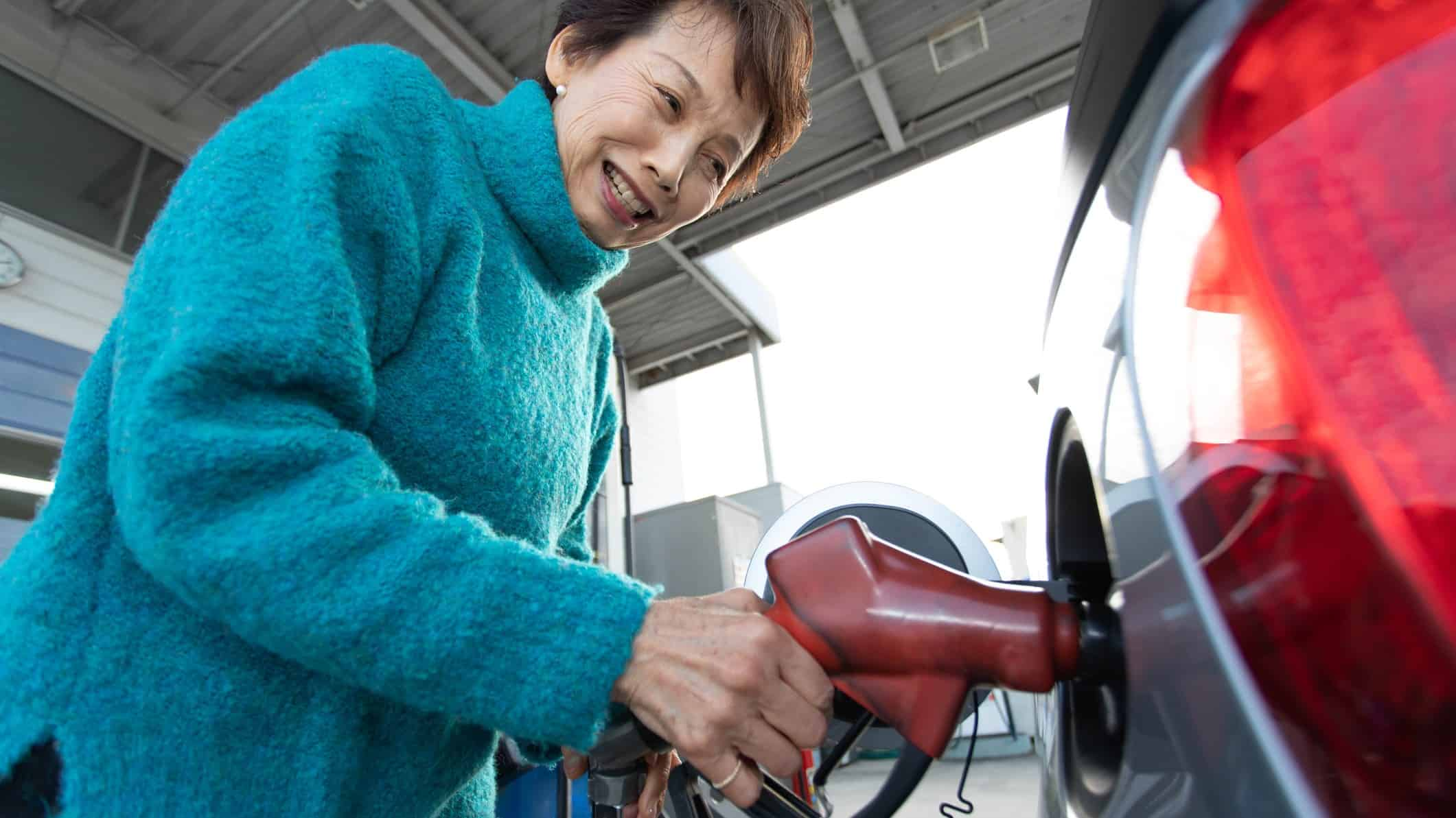 An older Asian woman fills up her car with petrol at the service station.