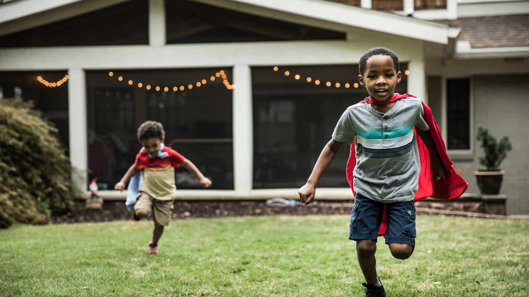 Two boys in capes running on the grass in front of their house.