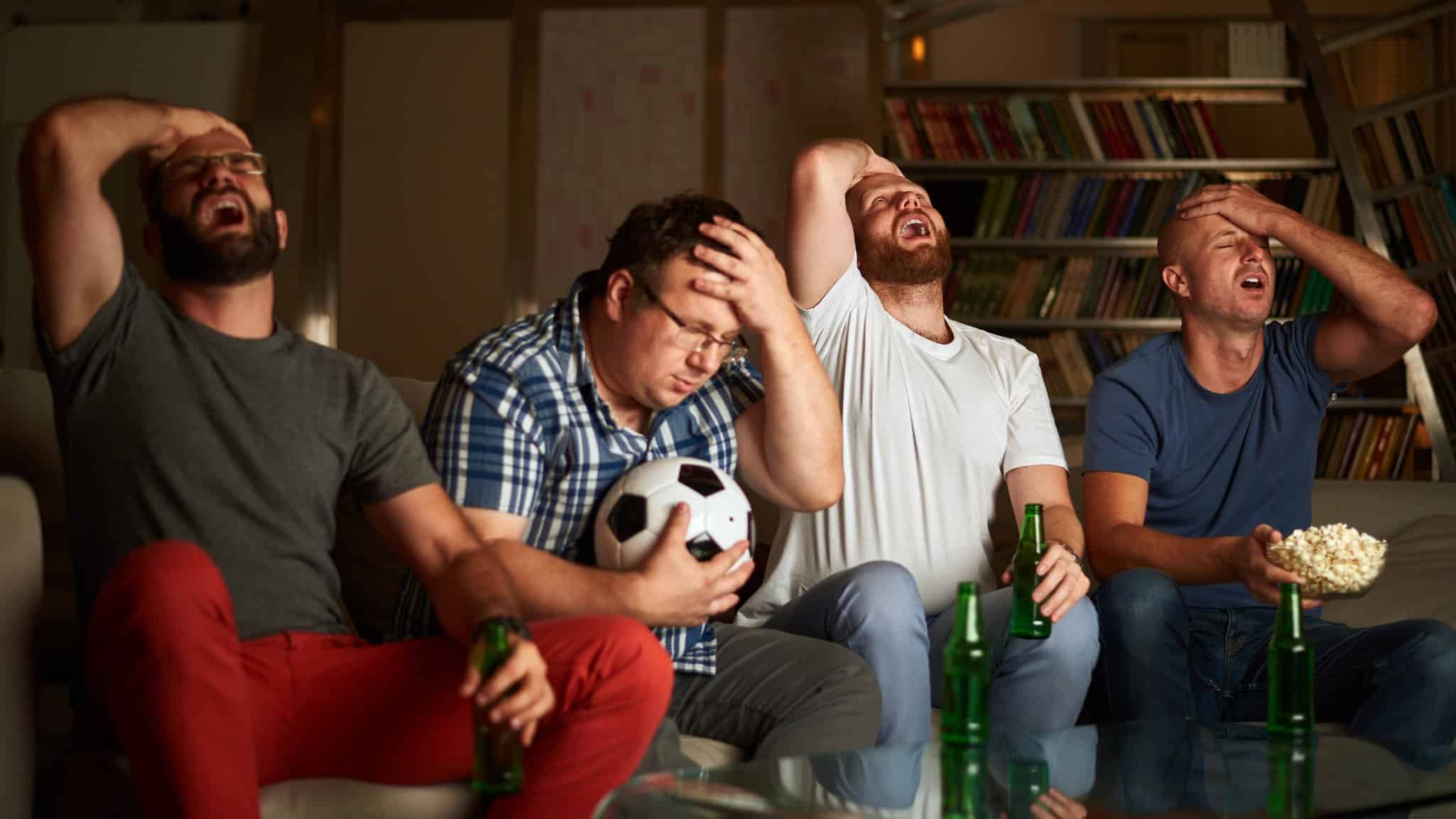 Four PointsBet customers and football fans put heads in hands and look disappointed while watching television
