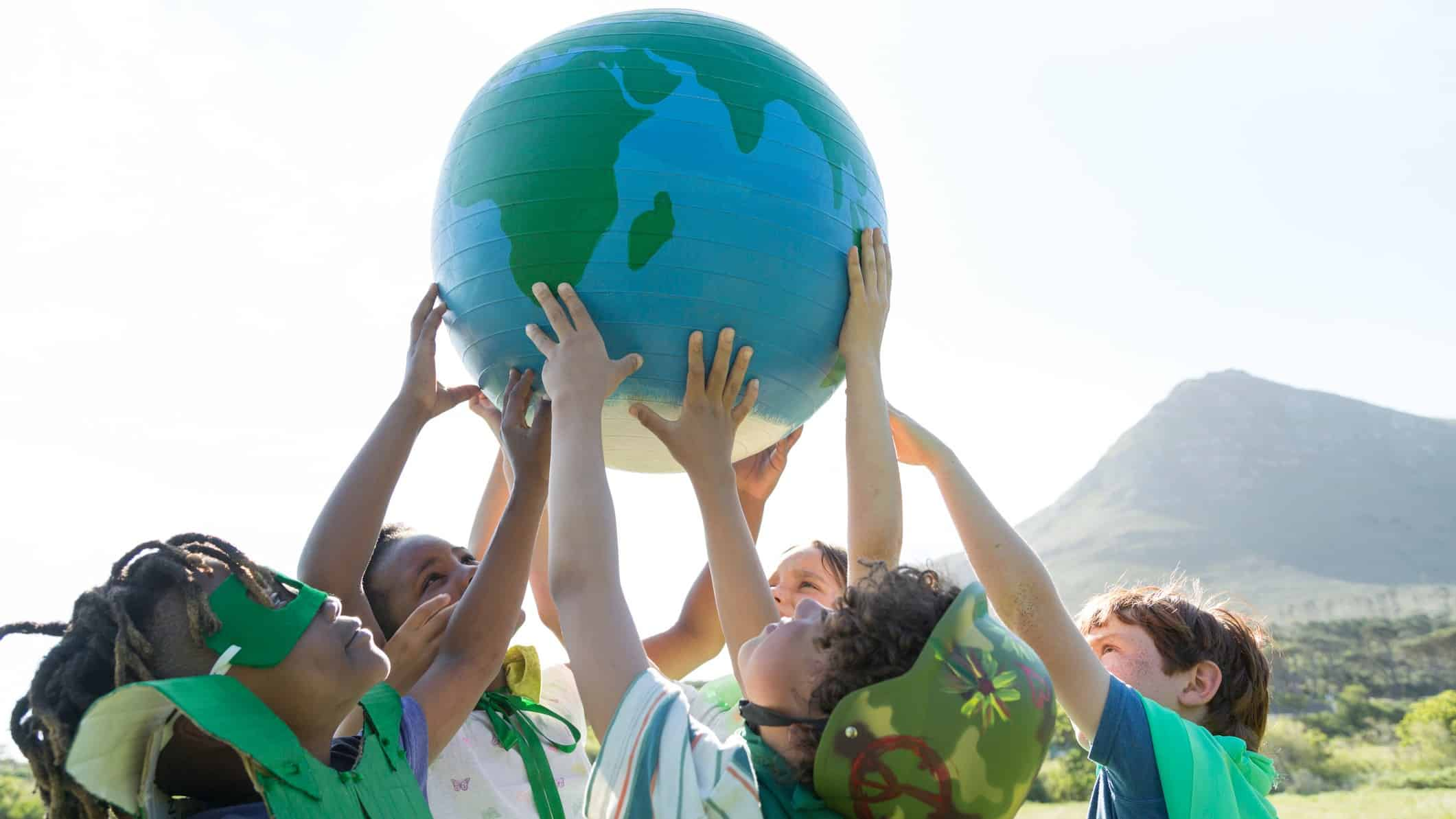 Group of children dressed in green hold up a globe relating to climate change.