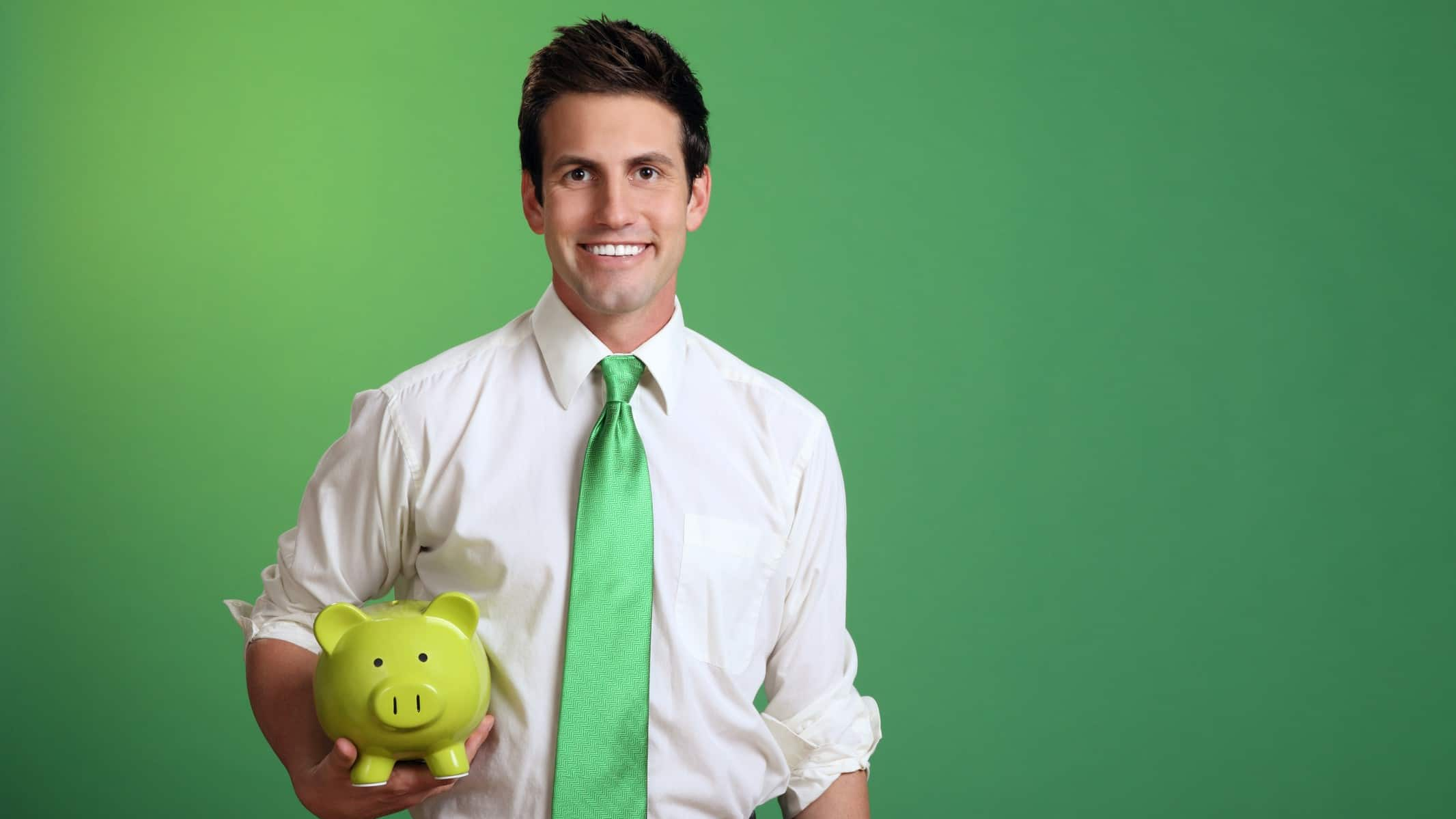 Young man in white shirt and green tie with green background holding green piggy bank