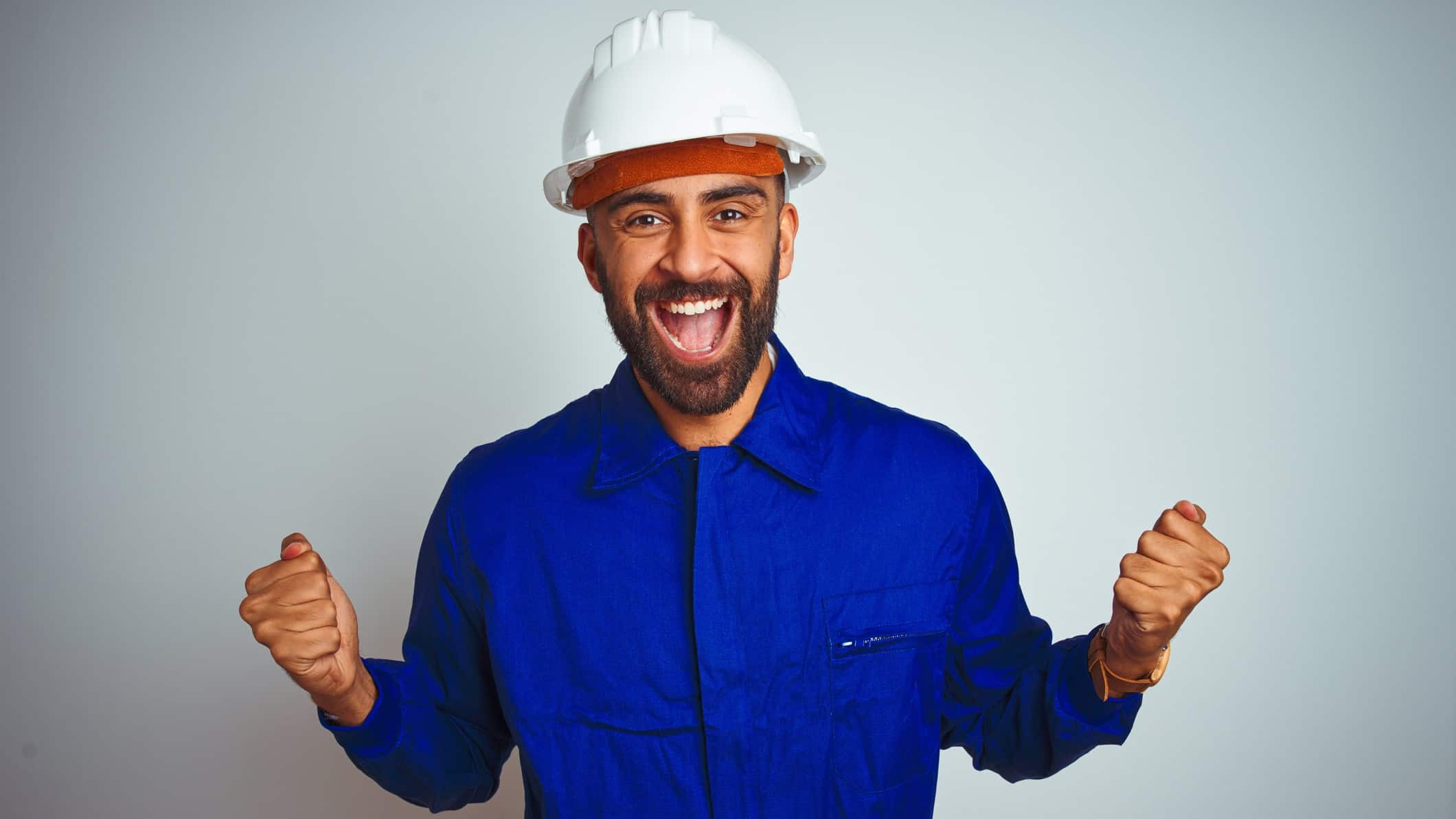 Man in white hard hat cheers with fists pumped