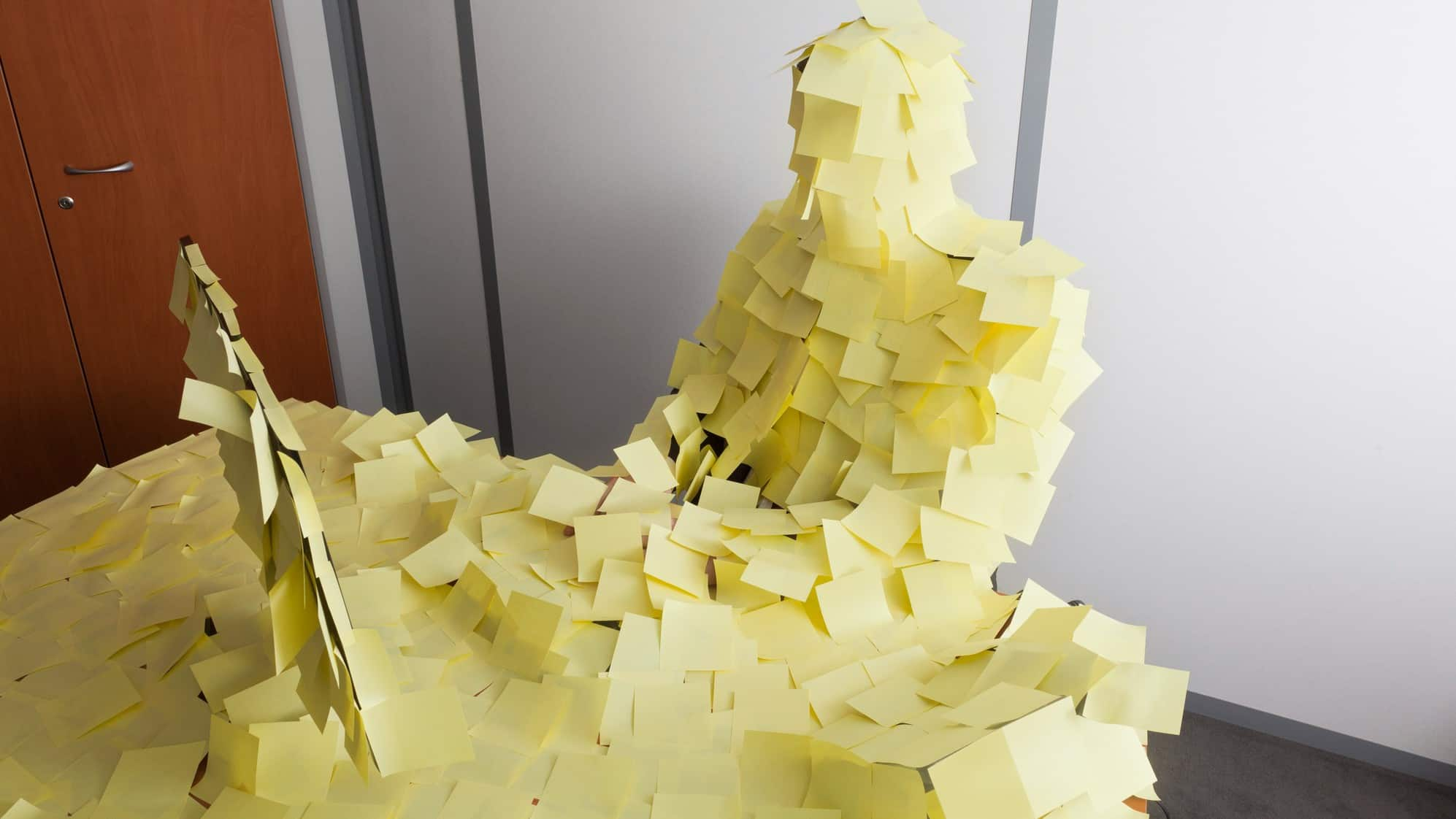 An office worker and his desk covered in yellow post-it notes