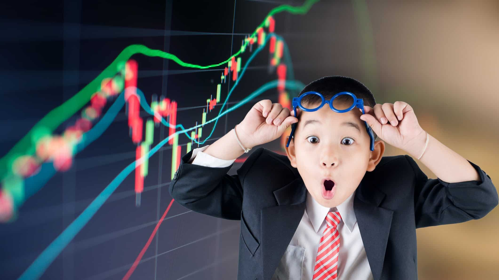 Young boy looks shocked as he lifts glasses above his eye in front of a stockmarket graph.