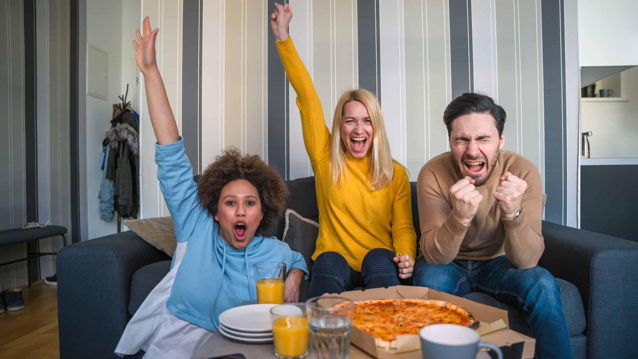 Three people sit on safe cheering with pizza on table