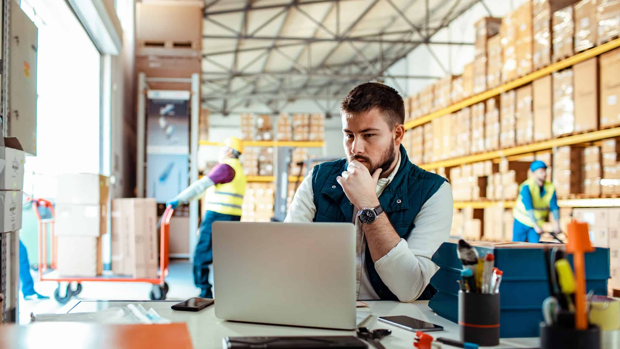 A warehouse manager sits at a desk in a warehouse looking at his computer