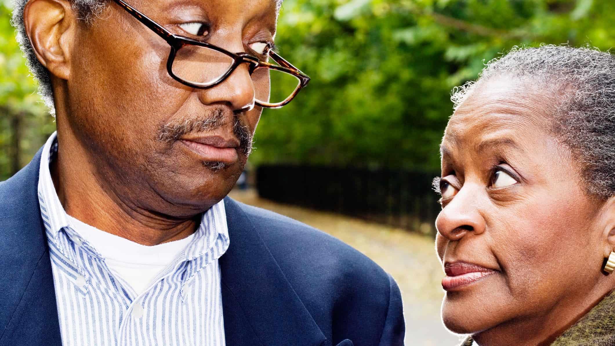 Elderly couple look sideways at each other in mild disagreement