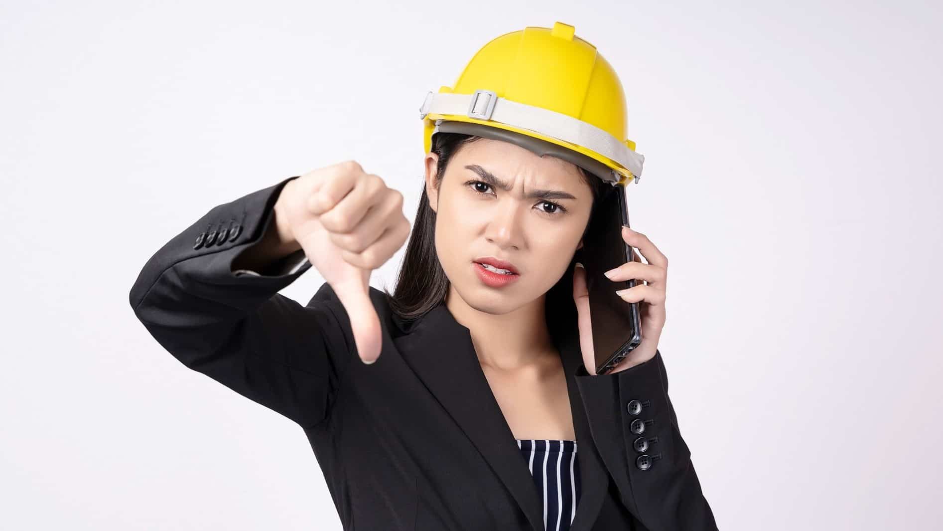Female worker in hard hat puts thumb down while on the phone