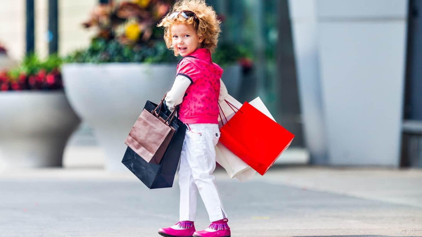 Young girl looks bag at camera as she walks in the street with several shopping bags.