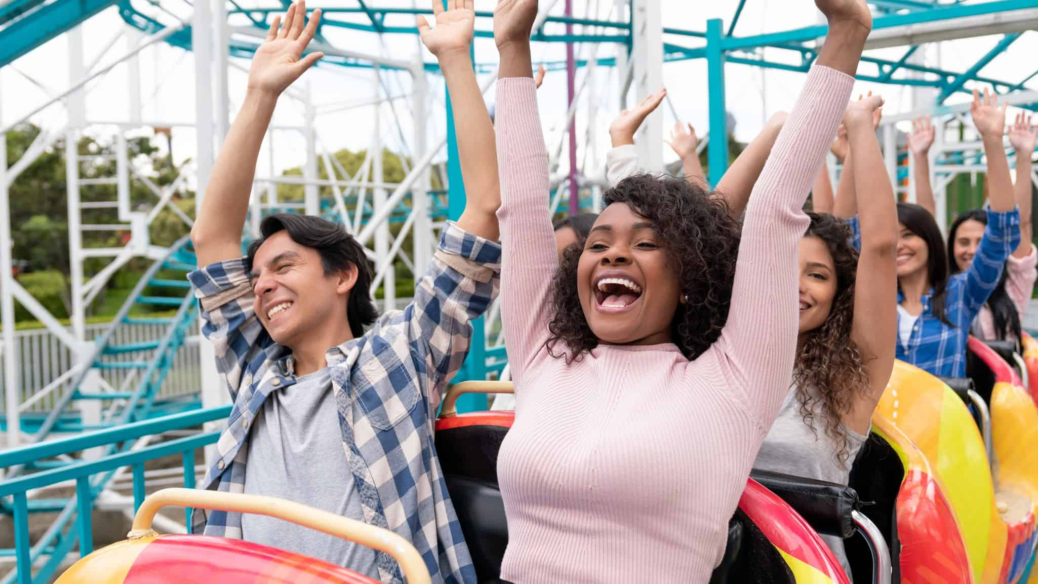 two people sit side by side on a rollercoaster ride with their hands raised in the air and happy smiles on their faces
