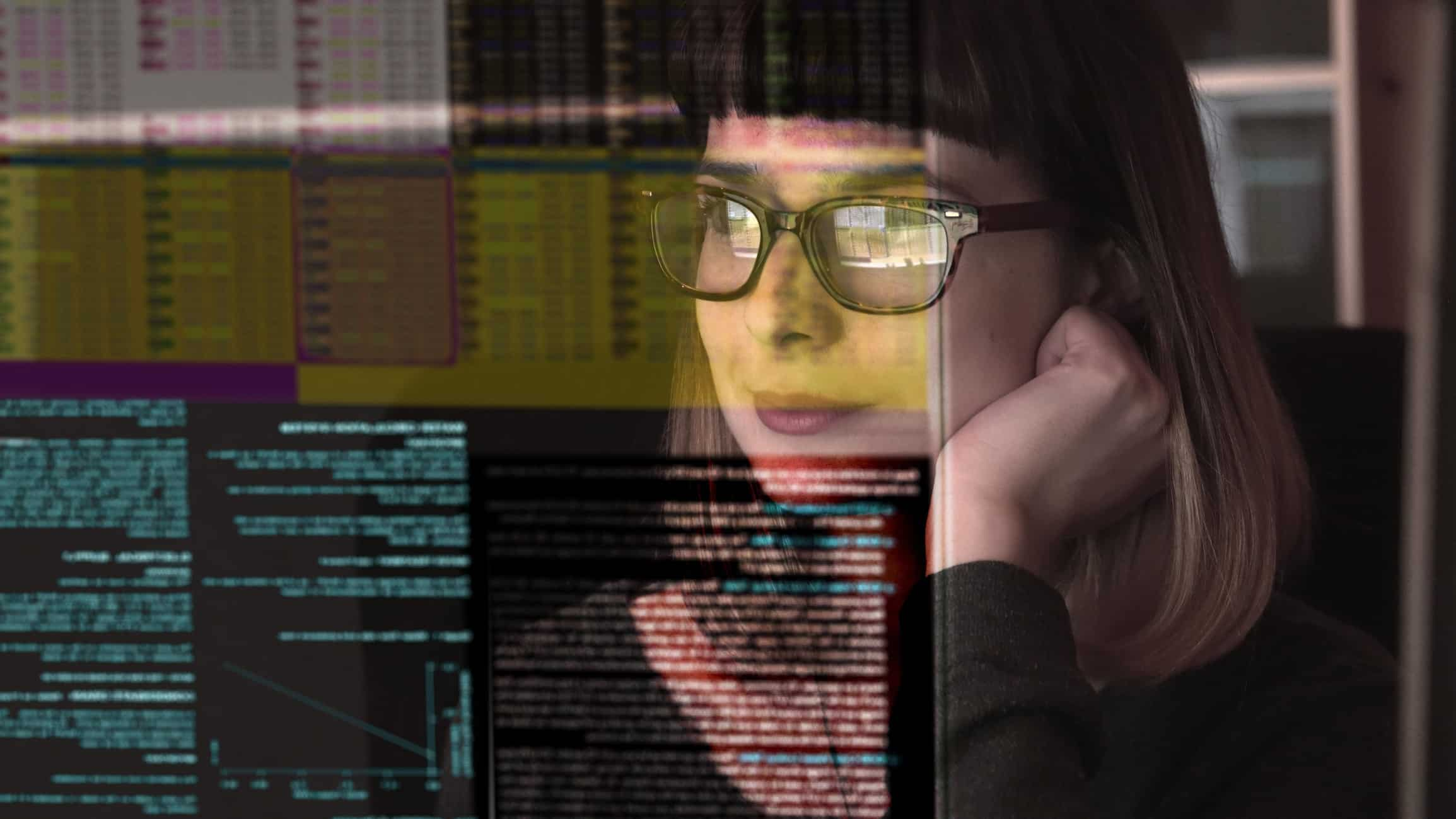 a woman with a small satisfied smile on her face looks at reflected, illuminated data on screens in front of her.