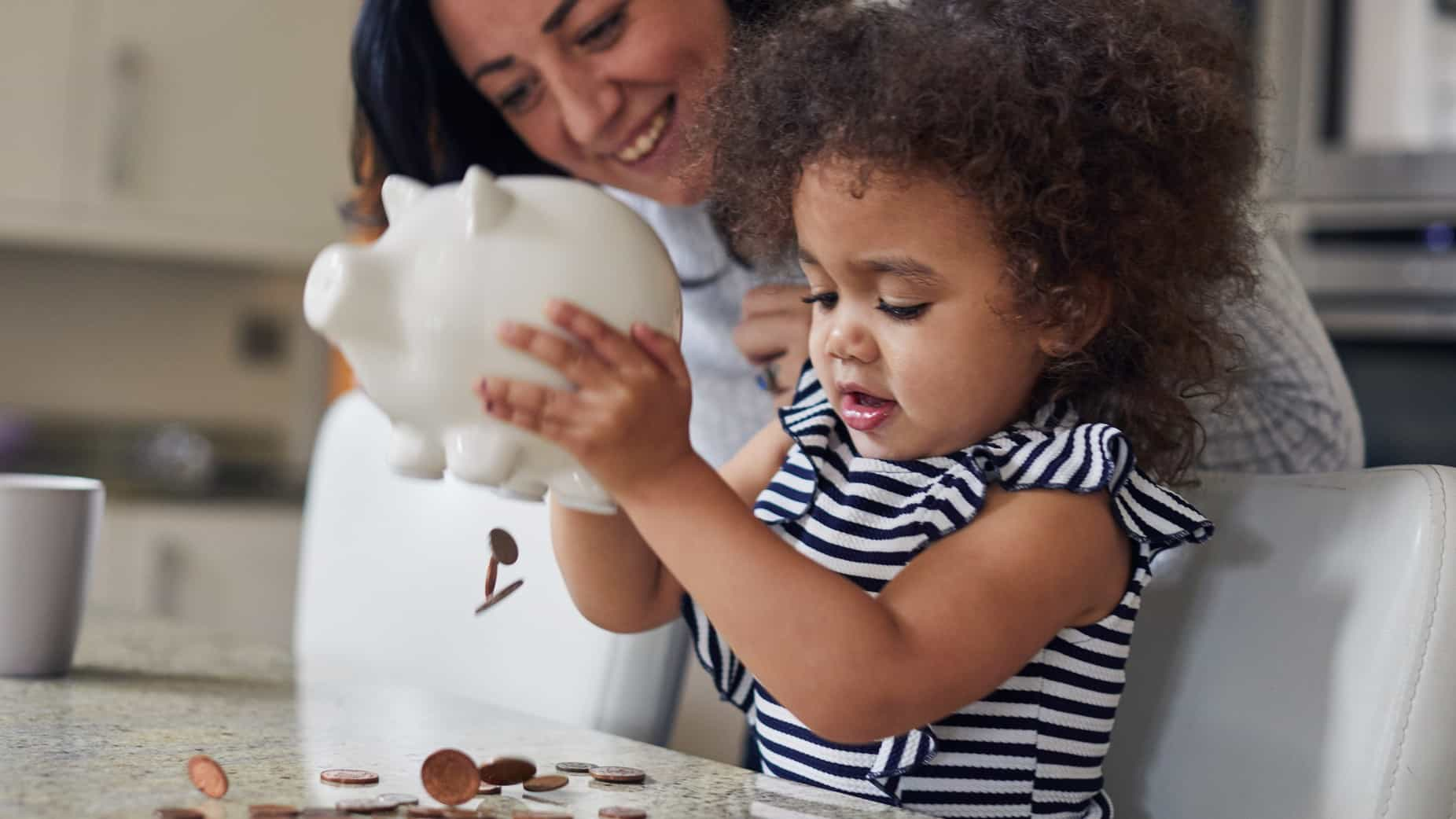 a small girl empties a piggy bank of coins onto a table while her mother looks on in the background.