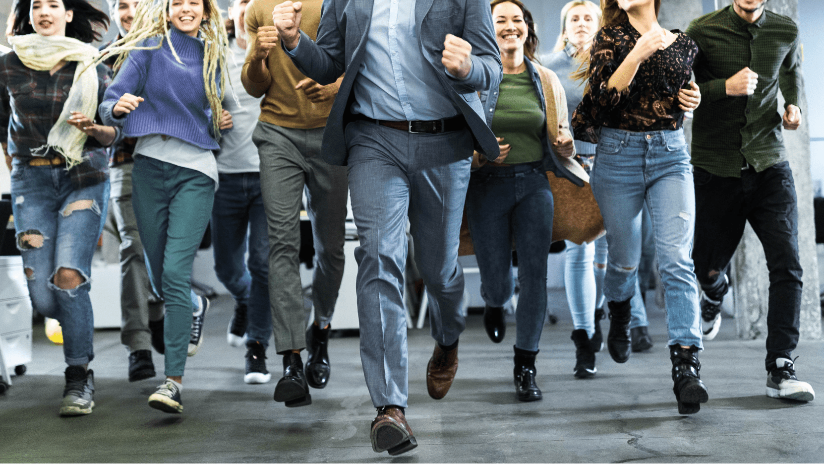 a group of people run towards the camera wearing business and smart casual clothes.