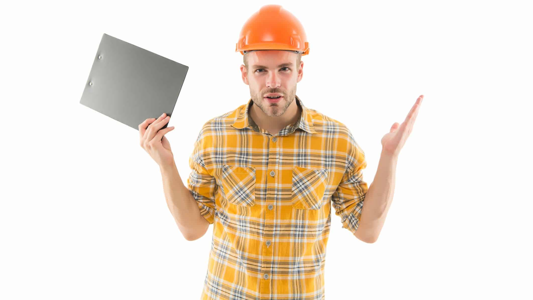 a man in a hard hat and checkered shirt holds paperwork in one hand as he holds his hands upwards in an enquiring manner as though asking a question or exasperated by uncertainty.
