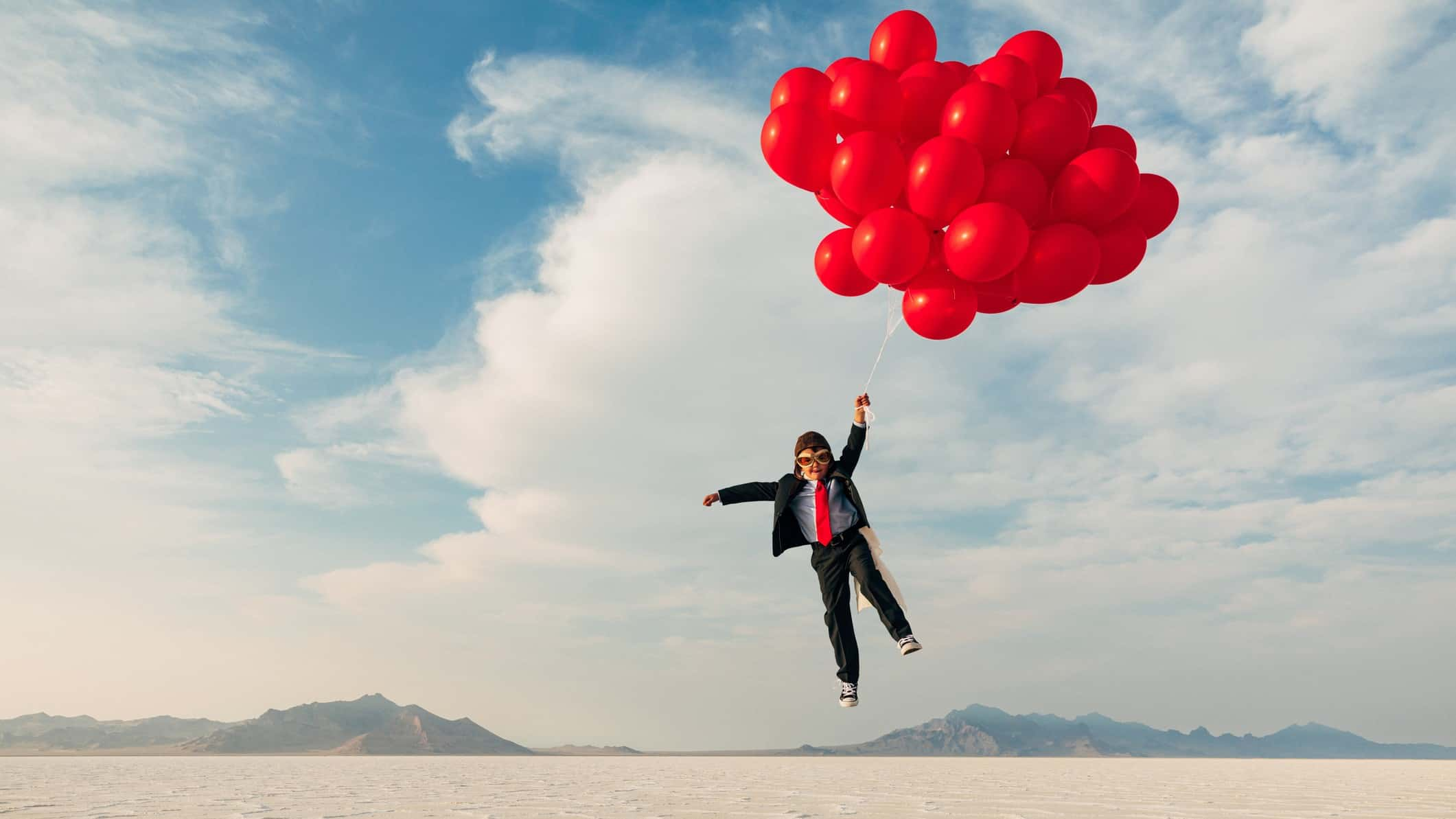 a boy dressed in a business suit and old fashioned flying helmet and goggles is lifted by a bunch of red helium balloons over a barren desert landscape.