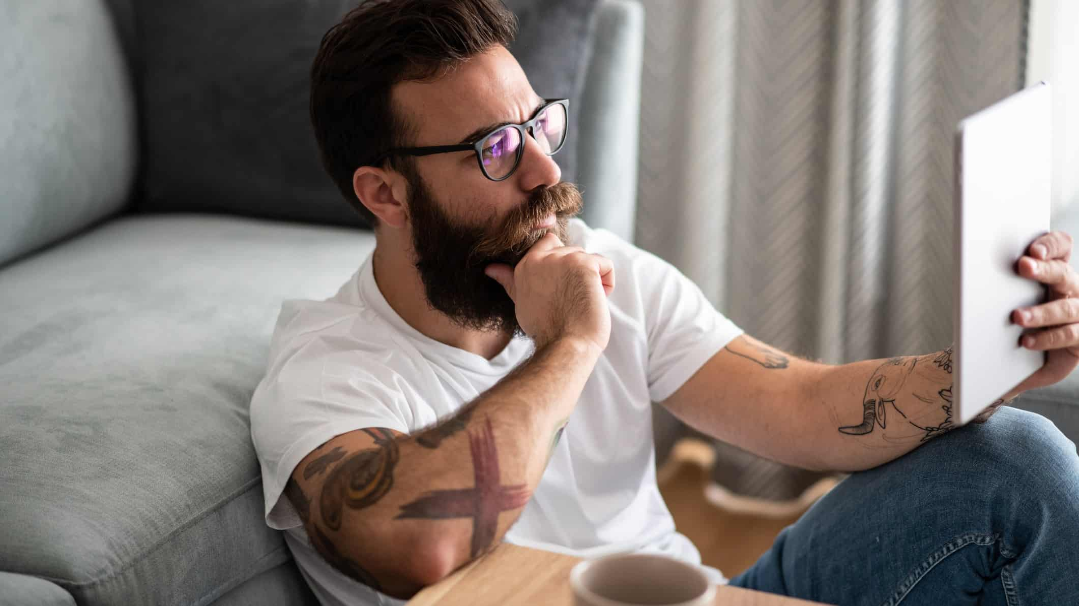 a hipster looking man with bushy beard and multiple arm tattoos sits on the floor against a sofa reading a tablet with his hand on his chin as though he is deep in thought.