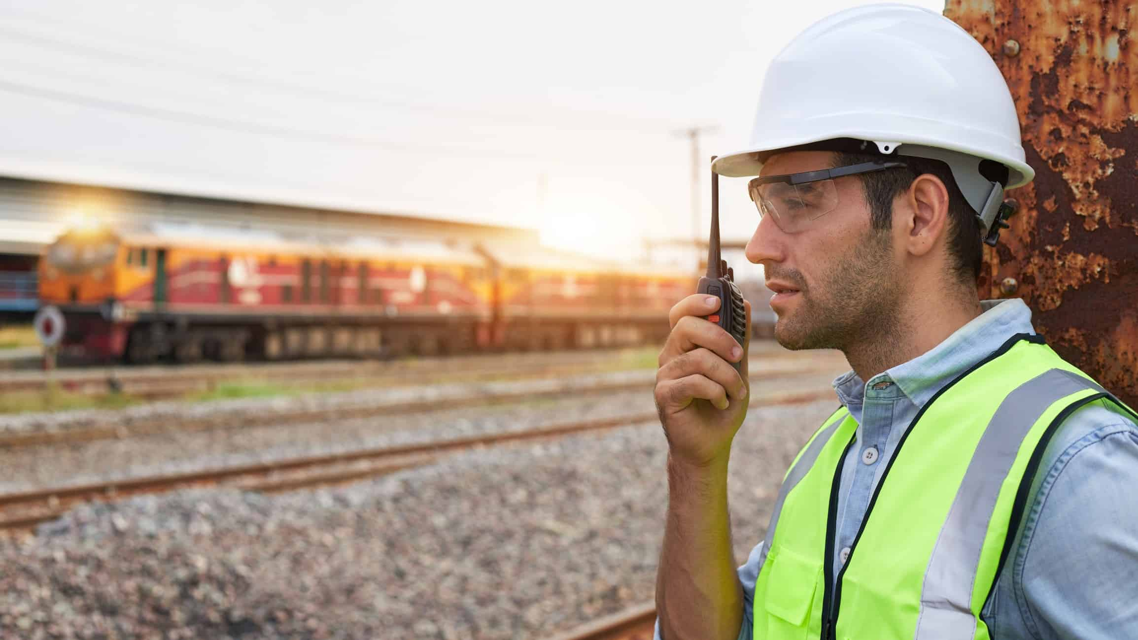 a man in hard hat and high visibility vest talks into a walky-talky device in the foreground of a freight train at a railway yard.