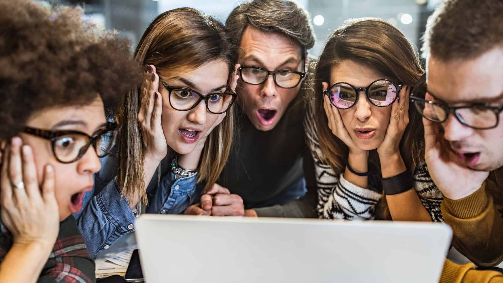 a group of people gathered around a laptop computer with various expressions of interest, concern and surpise on their faces. All are wearing spectacles.