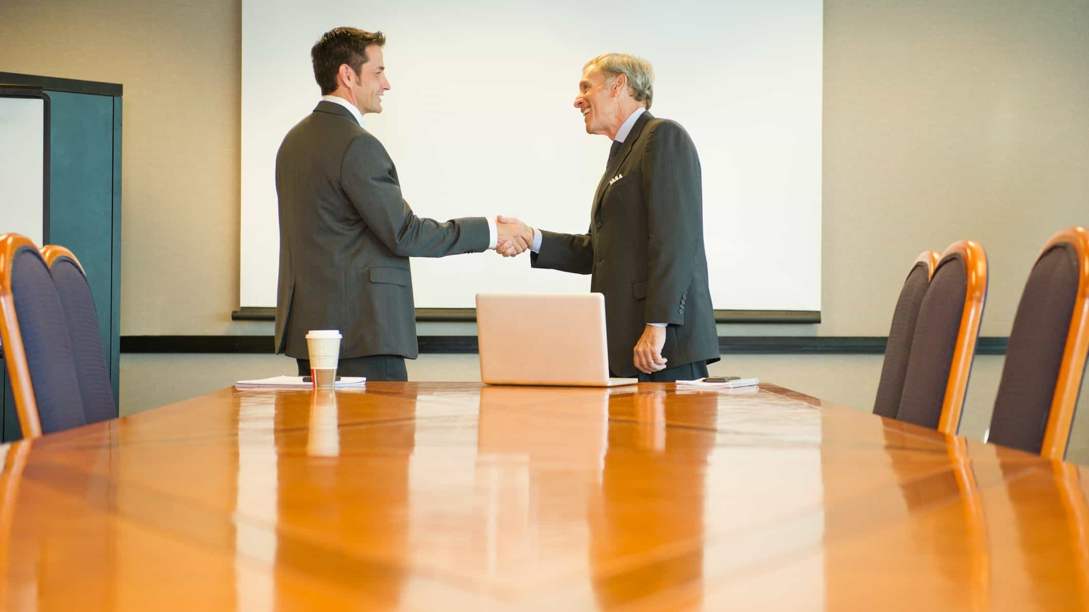 two men in suits shake hands at the top of a shined wood boardroom table.