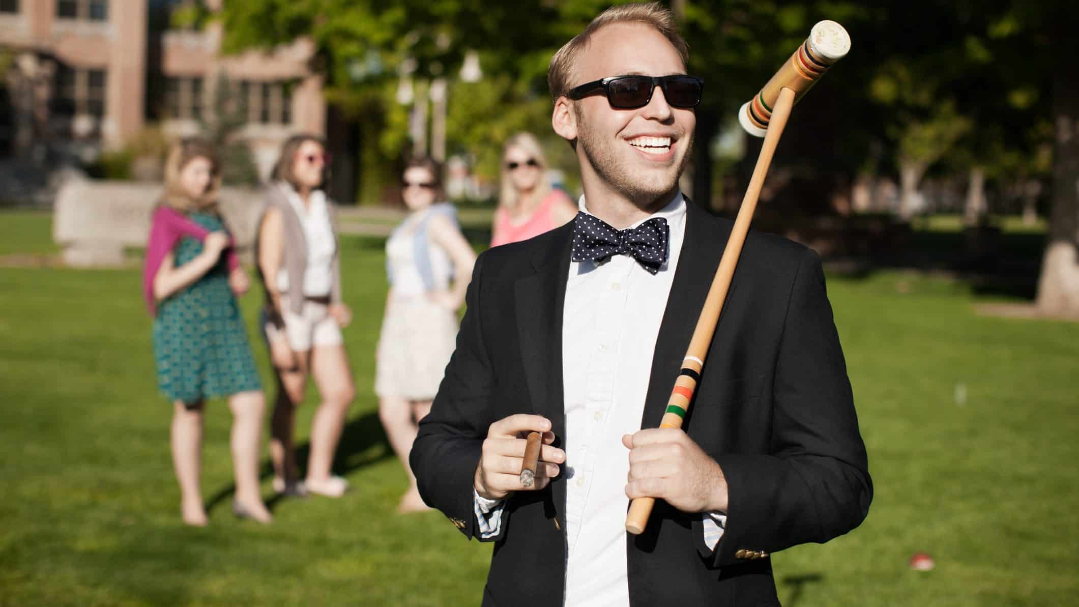 a man wearing a dinner suit holds a cigar and a croquet mallet on a rolling green lawn with a group of women and a mansion in the background.