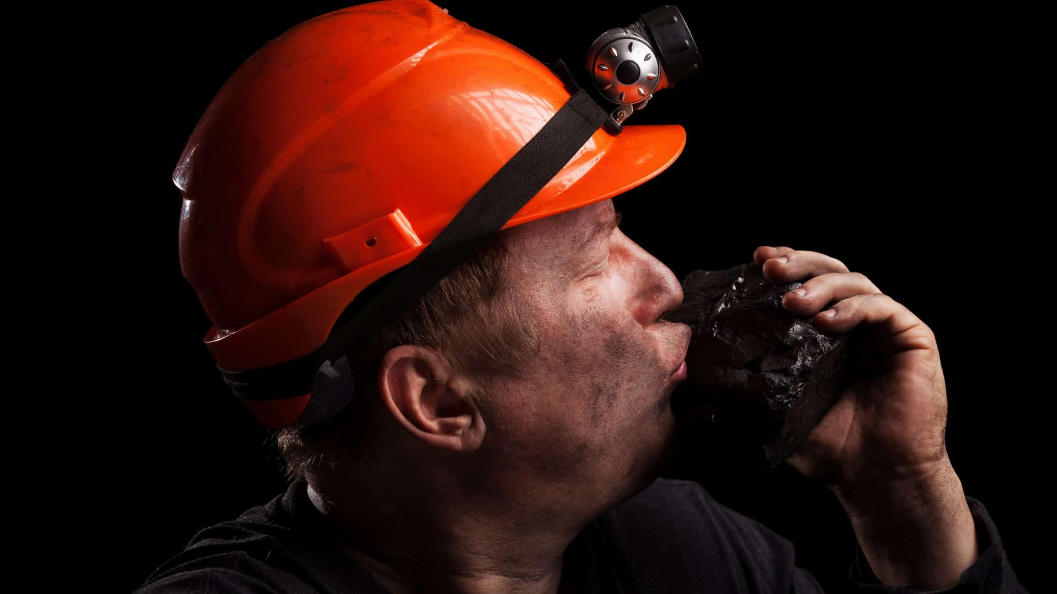 a coal miner in hard hat with a light on it kisses a large lump of coal that he is holding in his hand.