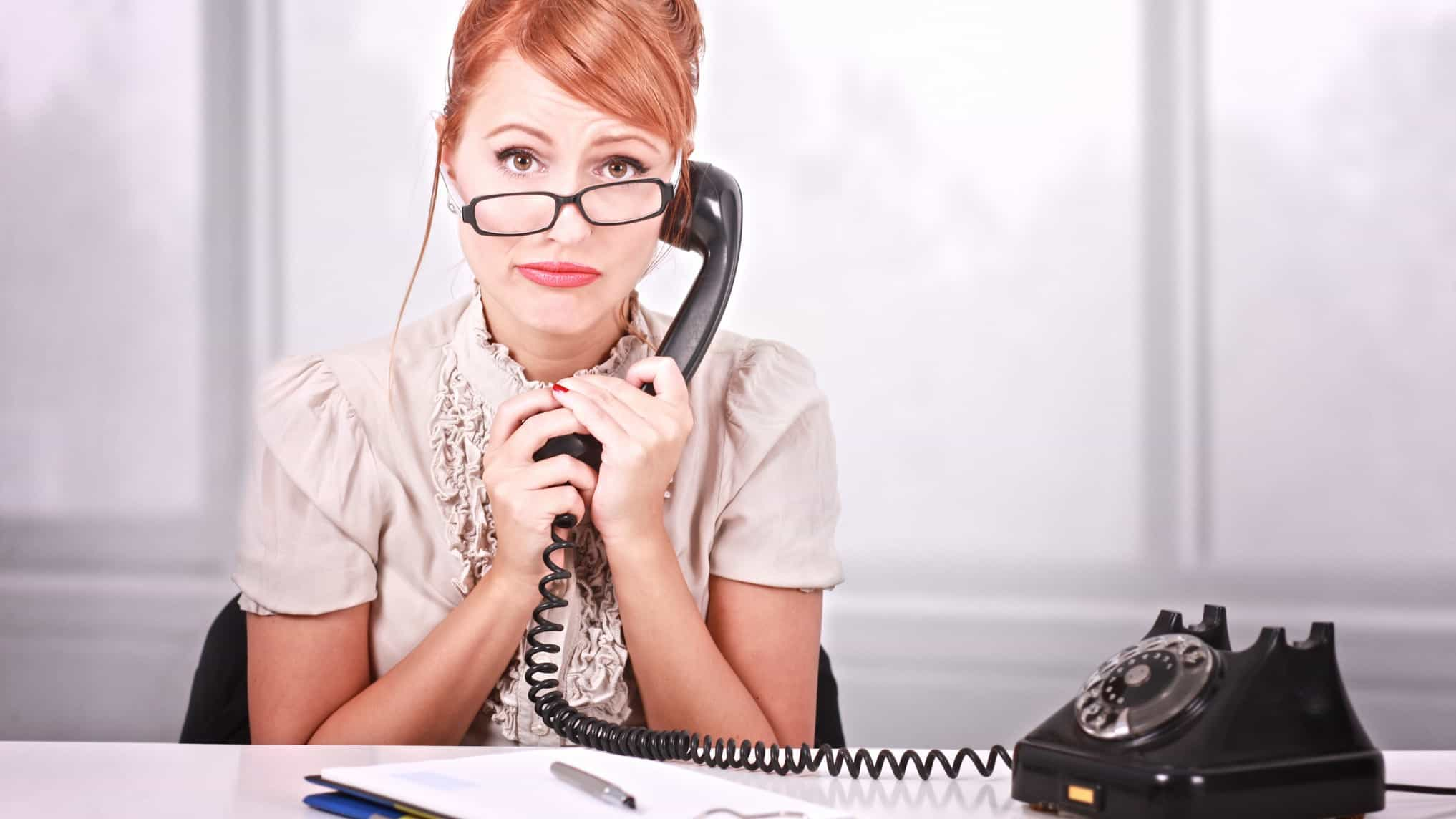 a woman holds an old fashioned telephone ear piece to her ear while looking unhappy sitting at a desk with her glasses crooked on her nose and a deflated expression on her face.