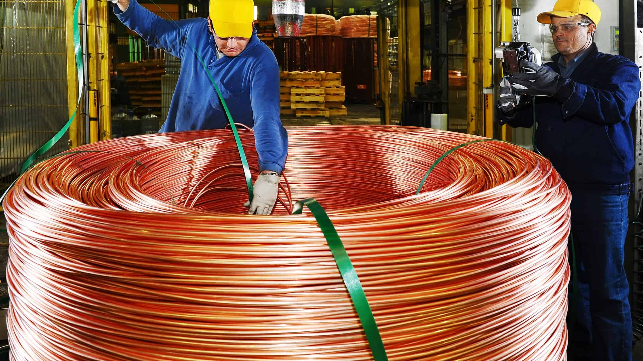 workers stand over a large spool of copper pipe.