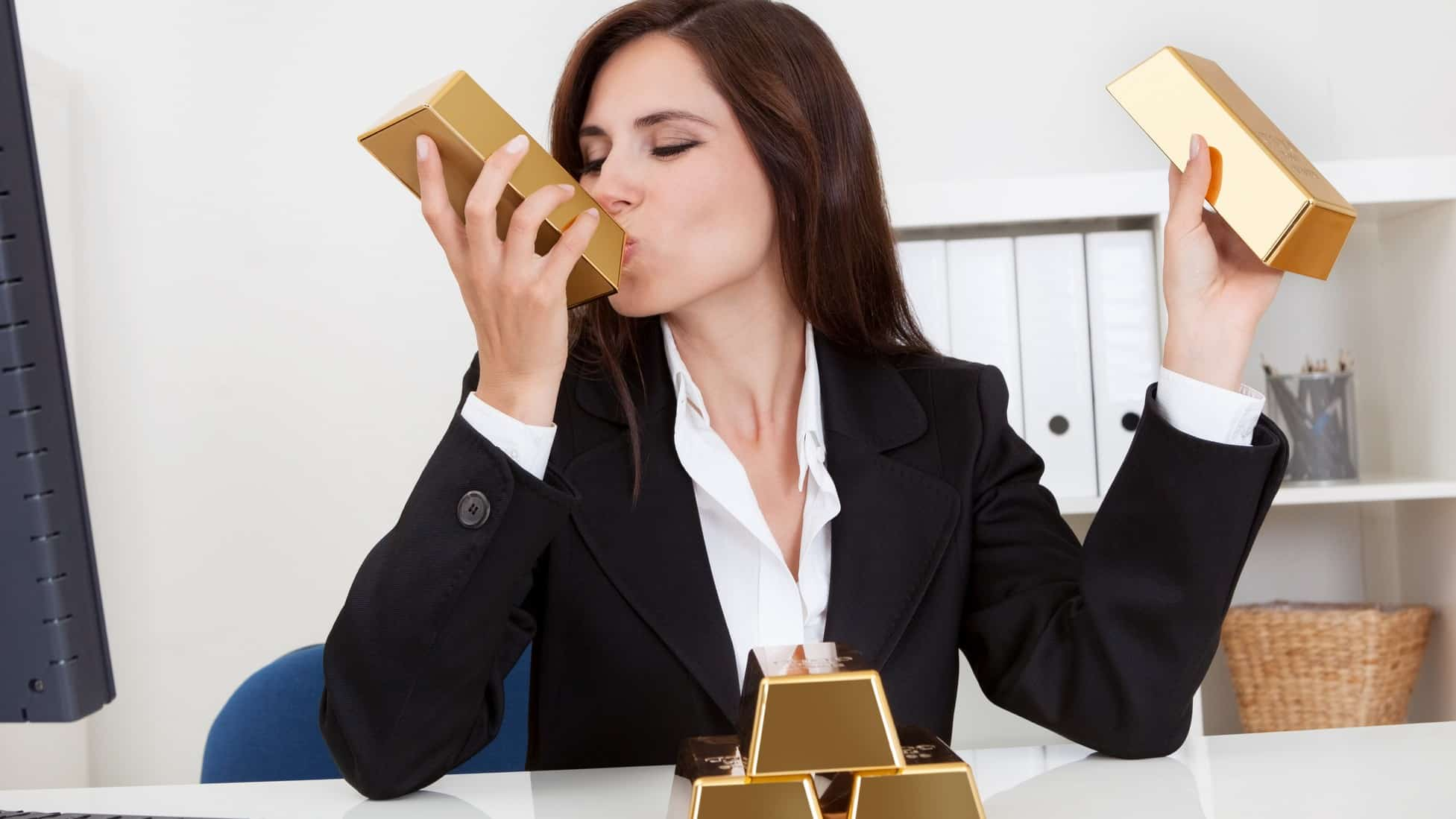 a woman in a business suit sits at her desk with gold bars in each hand while she kisses one with her eyes closed. Her desk has another three gold bars stacked in front of her.