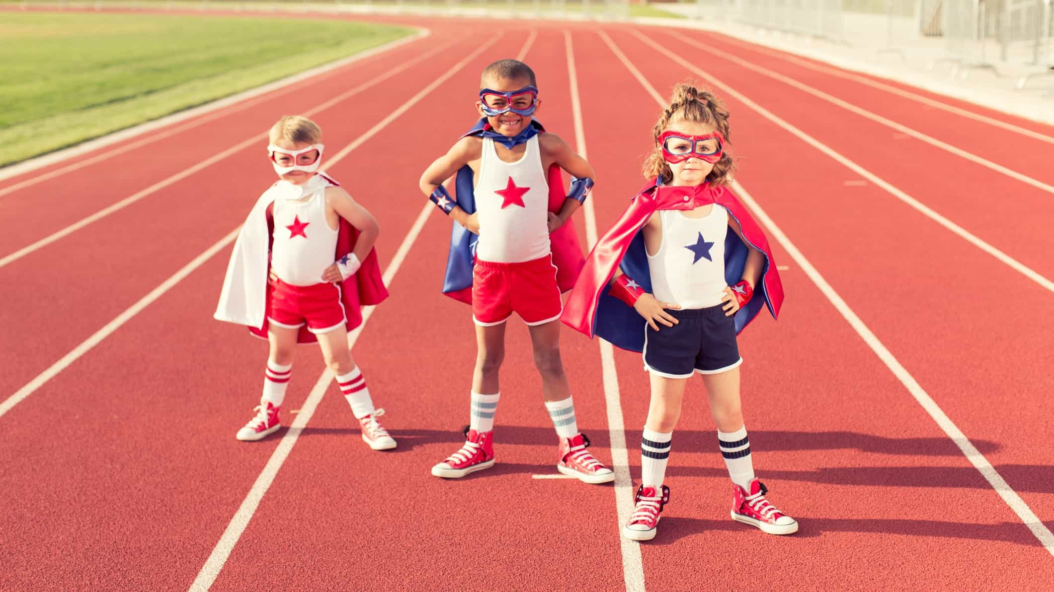 three children wearing superhero costumes, complete with masks, pose with hands on hips wearing capes and sneakers on a running track.