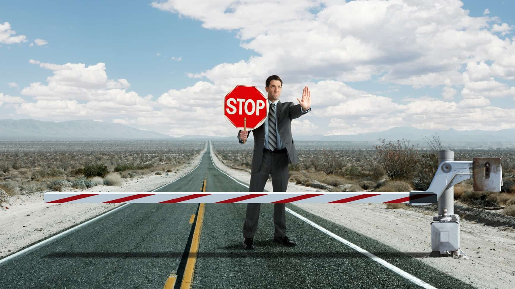 a man in a suit holds up a hand and a stop sign at a roadblock positioned over a bitumen road .