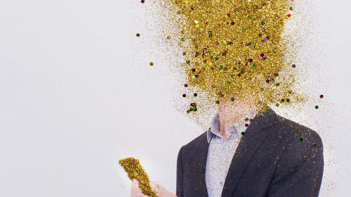 a man in a business suit looks at a gold phone with his head in an exploding clould of gold dust.